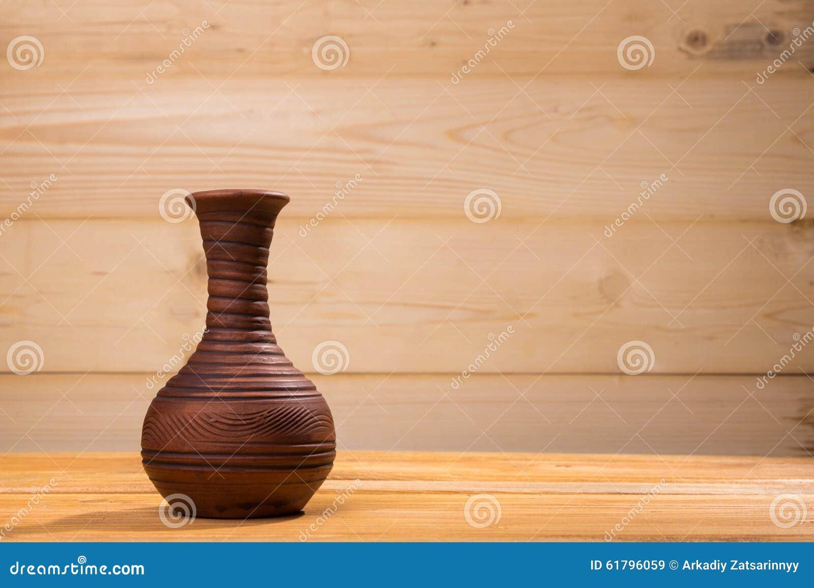 Ceramiczna butelka na drewnianym tle