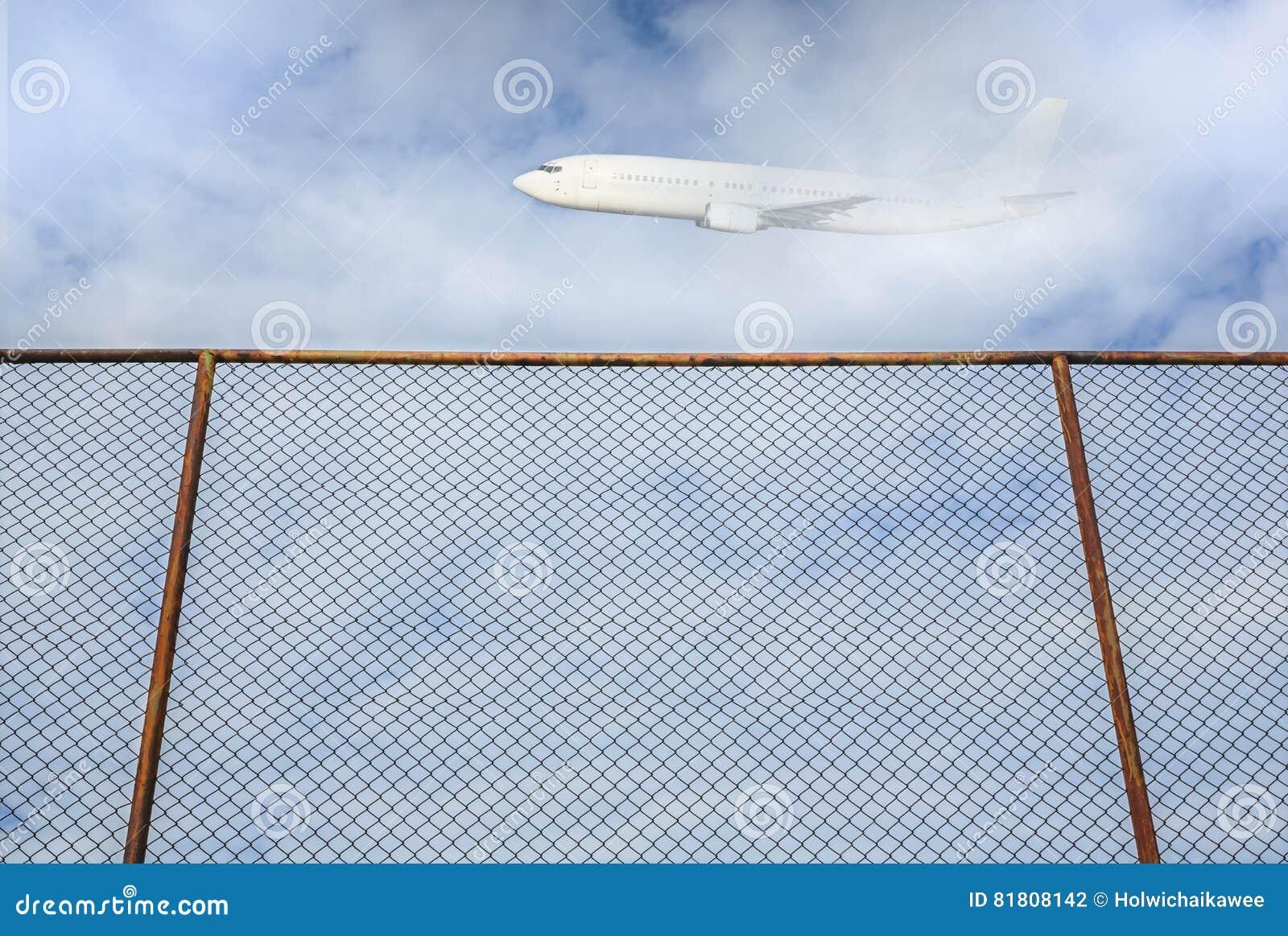 Cerca de aço velha com voo plano no céu