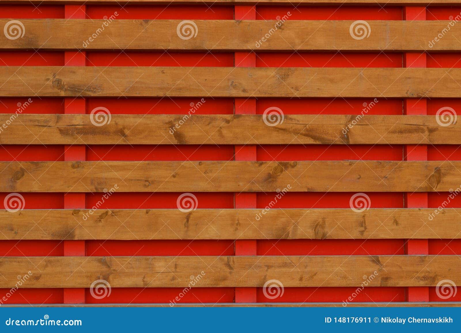 Cerca de madeira com placas horizontais do fundo vermelho