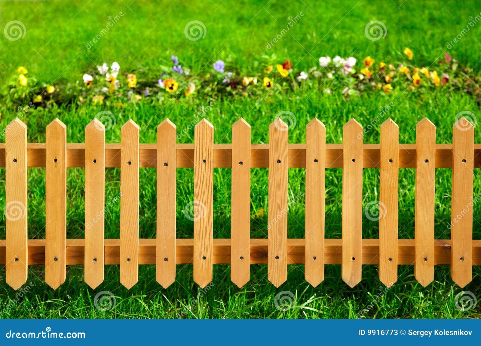 Cerca de madeira do jardim de encontro à grama verde e às flores