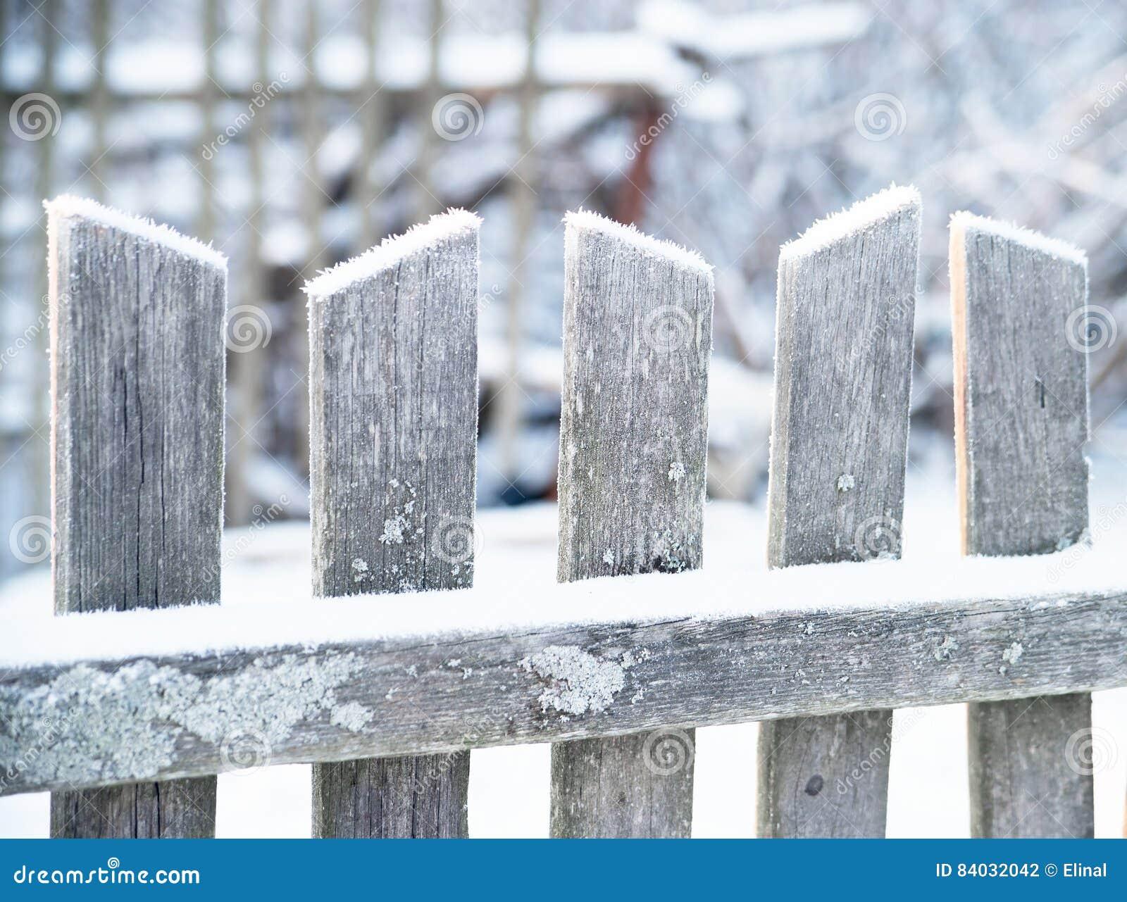 Cerca de madera vieja en invierno Escarchado, nieve