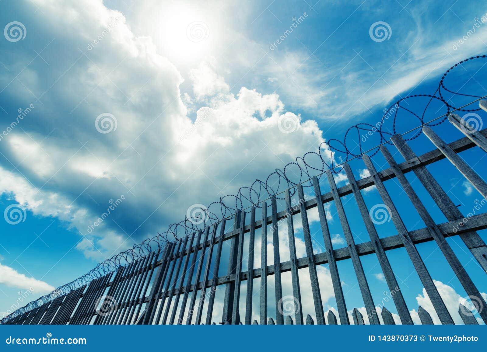 Cerca do arame farpado que cerca complexo da prisão, o militar ou o outro de alta segurança