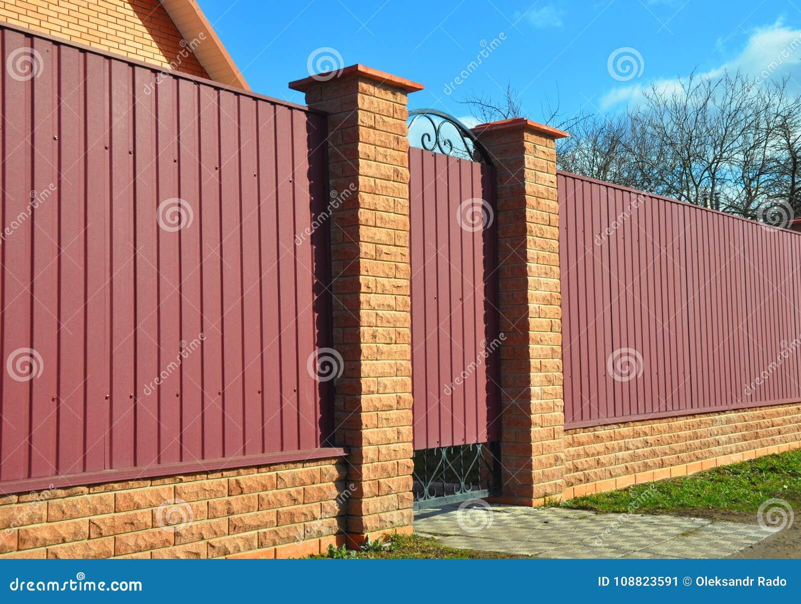 Cerca do tijolo e do metal com porta e porta Cercando a construção