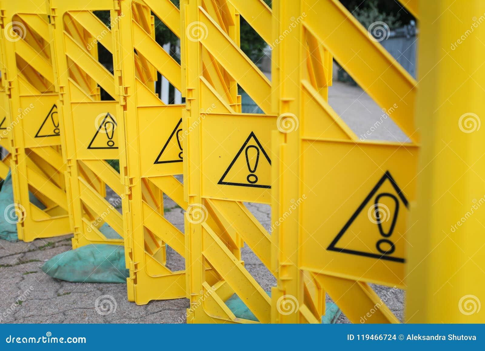 Cerca plástica amarilla con las marcas de exclamación, concepto de prohibición, atención de la paga
