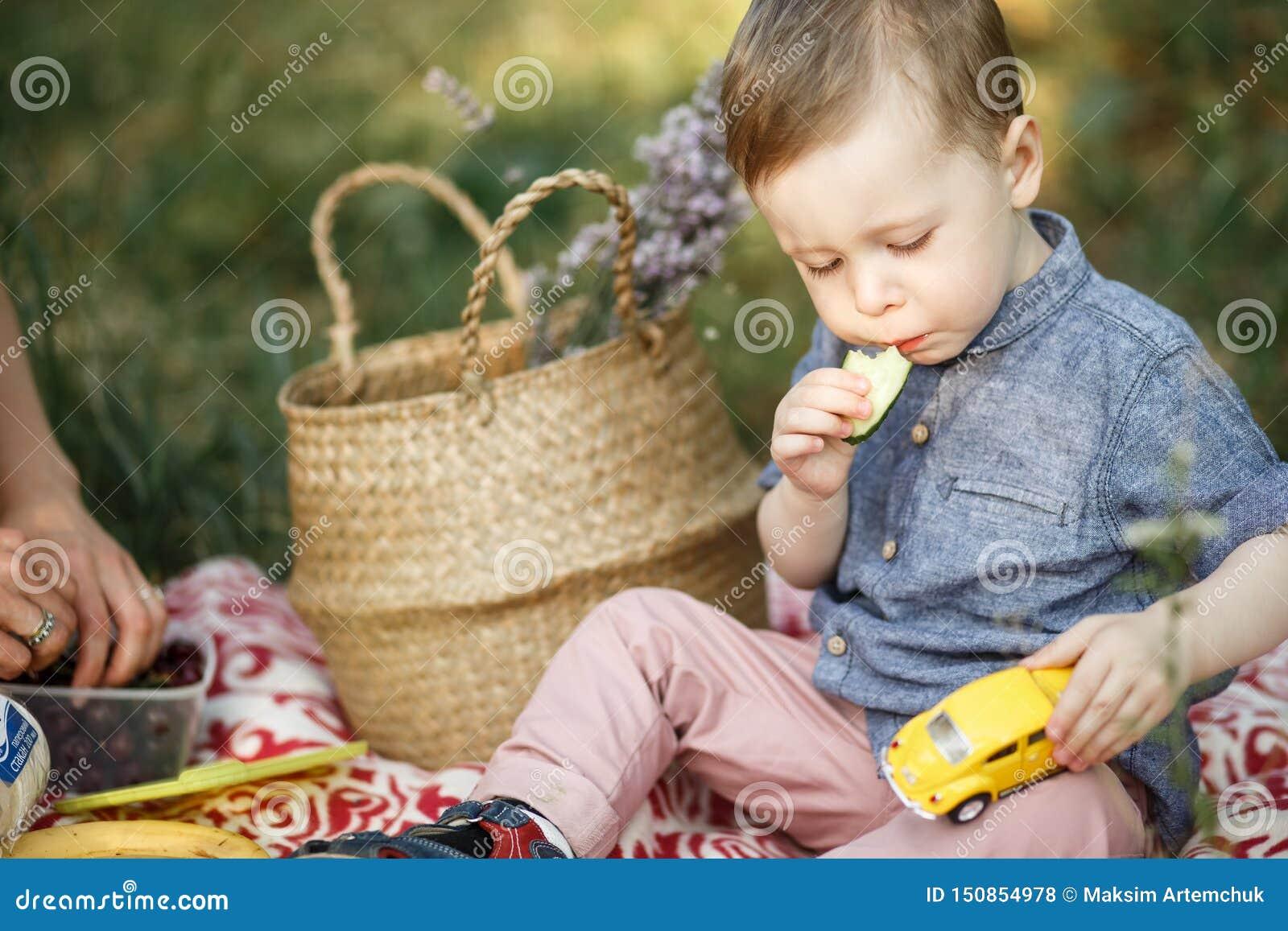 Cerca se está sentando en la manta y está jugando con el juguete Él tiene coche amarillo en su siesta También el niño está comien