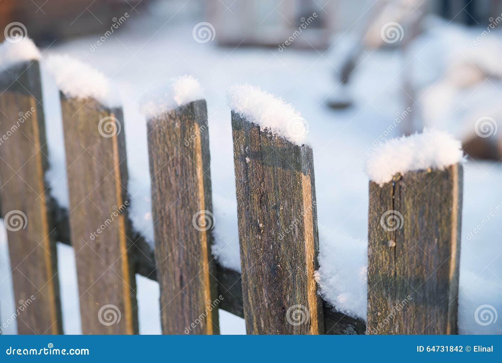 Cerca velha de madeira com neve Inverno