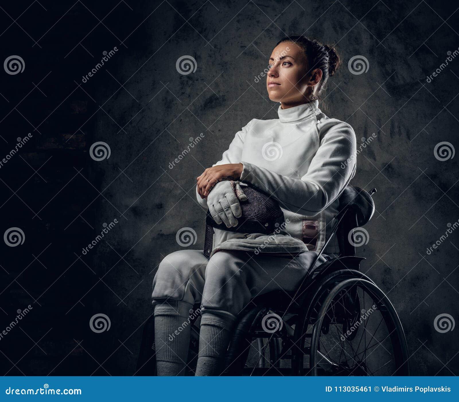 Cercador de sexo femenino en silla de ruedas con la máscara y el estoque de la seguridad
