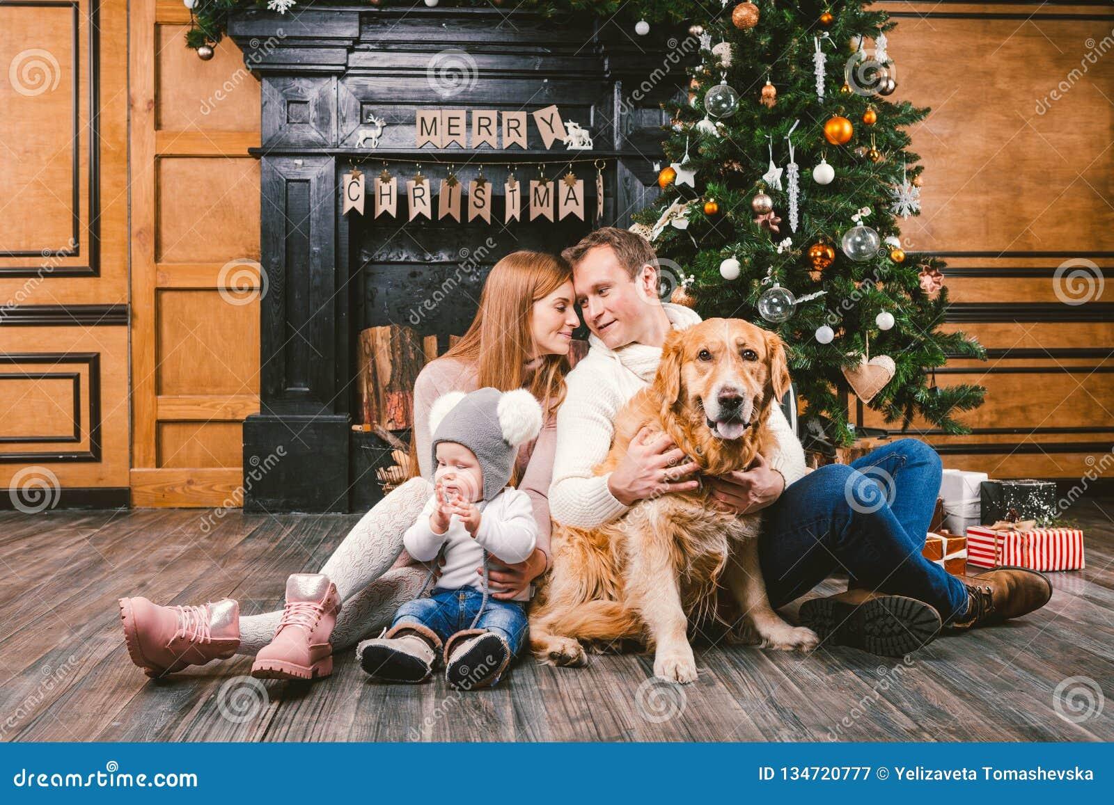 Cercle de famille de Noël de thème et de nouvelle année Jeune famille caucasienne avec le golden retriever de 1 an de Labrador de