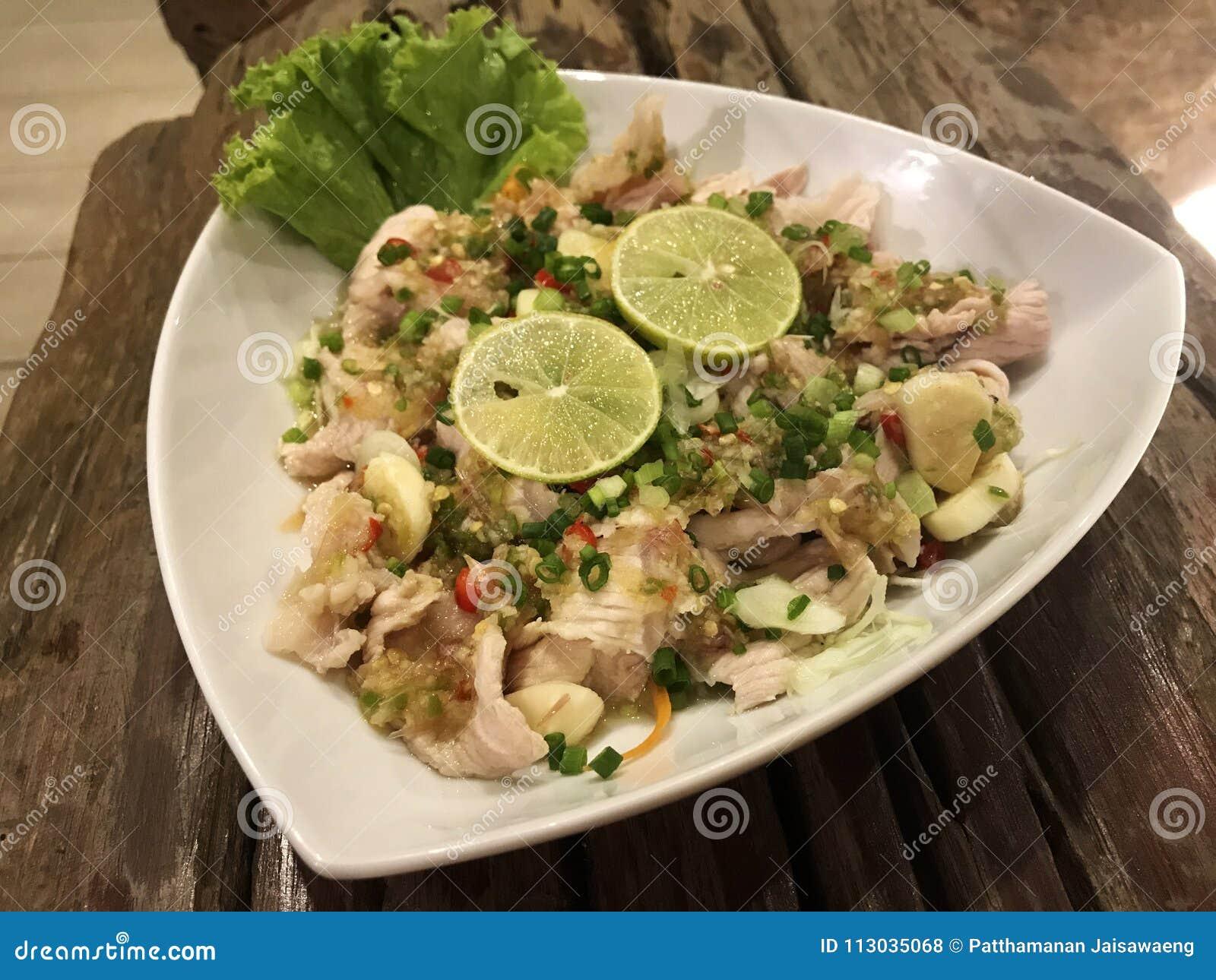 Cerdo con la salsa dulce picante del limón en el plato blanco