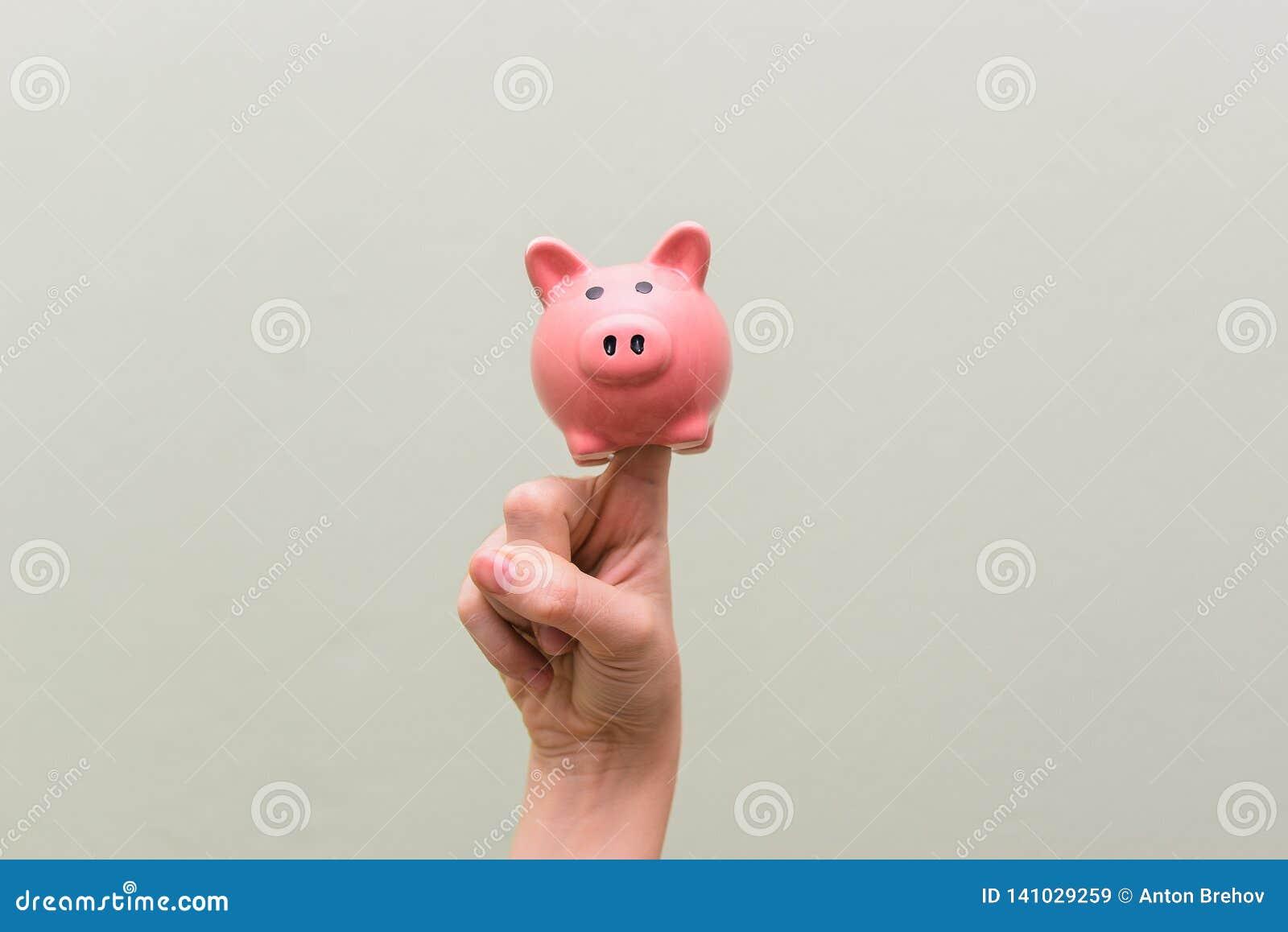 Cerdo de la porcelana en el dedo índice El concepto de dinero del ahorro Tema financiero