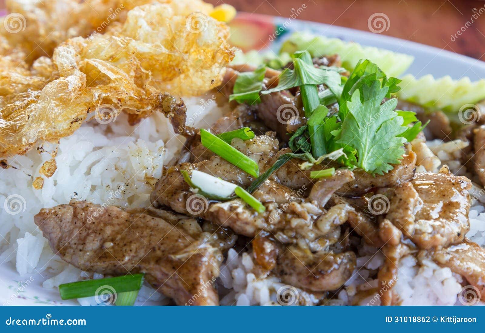 Cerdo frito con ajo y el huevo en el arroz