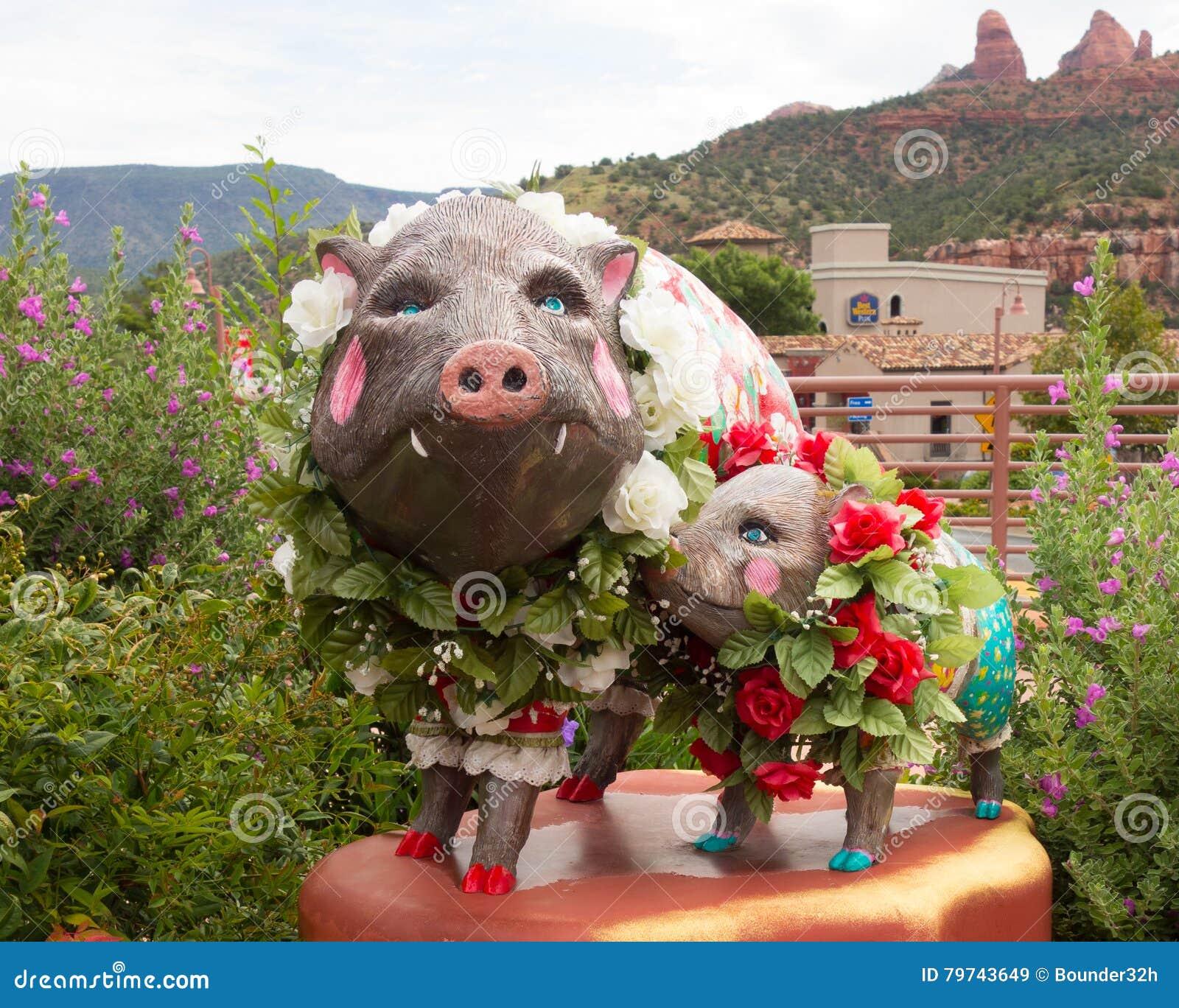 Cerdos artísticos cubiertos con las flores delante de una tienda en sedona