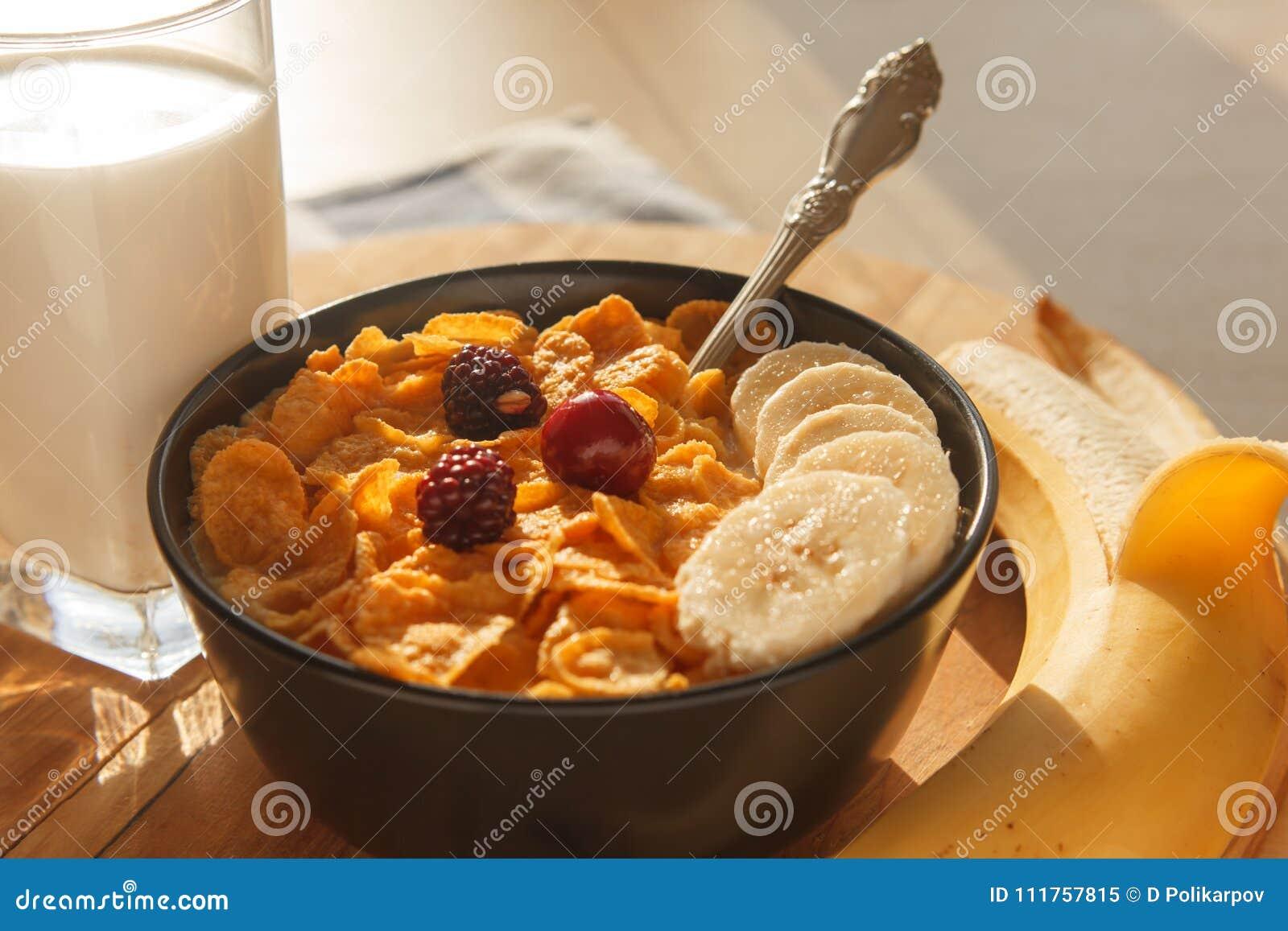 Cereal de desayuno de los copos de maíz en el cuenco con el vidrio de la leche, de bayas y del plátano en la tabla de madera