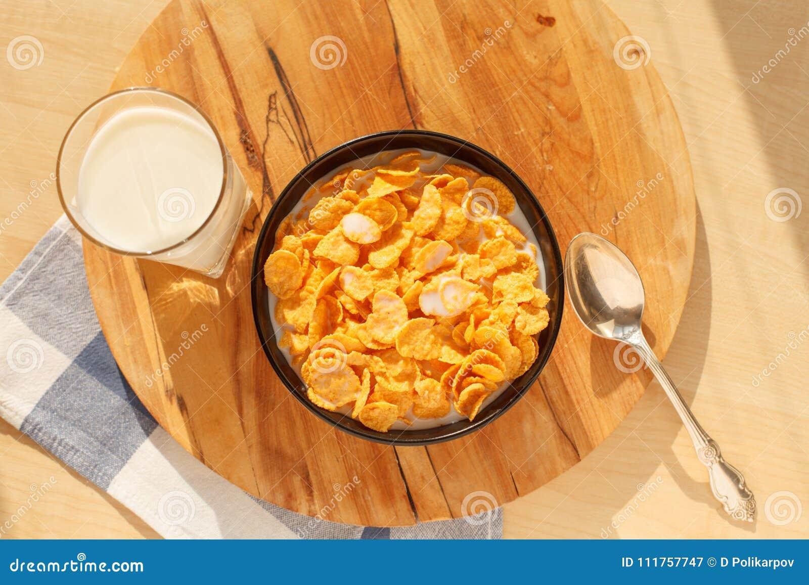 Cereal de desayuno de los copos de maíz en el cuenco con el vidrio de leche en la tabla de madera