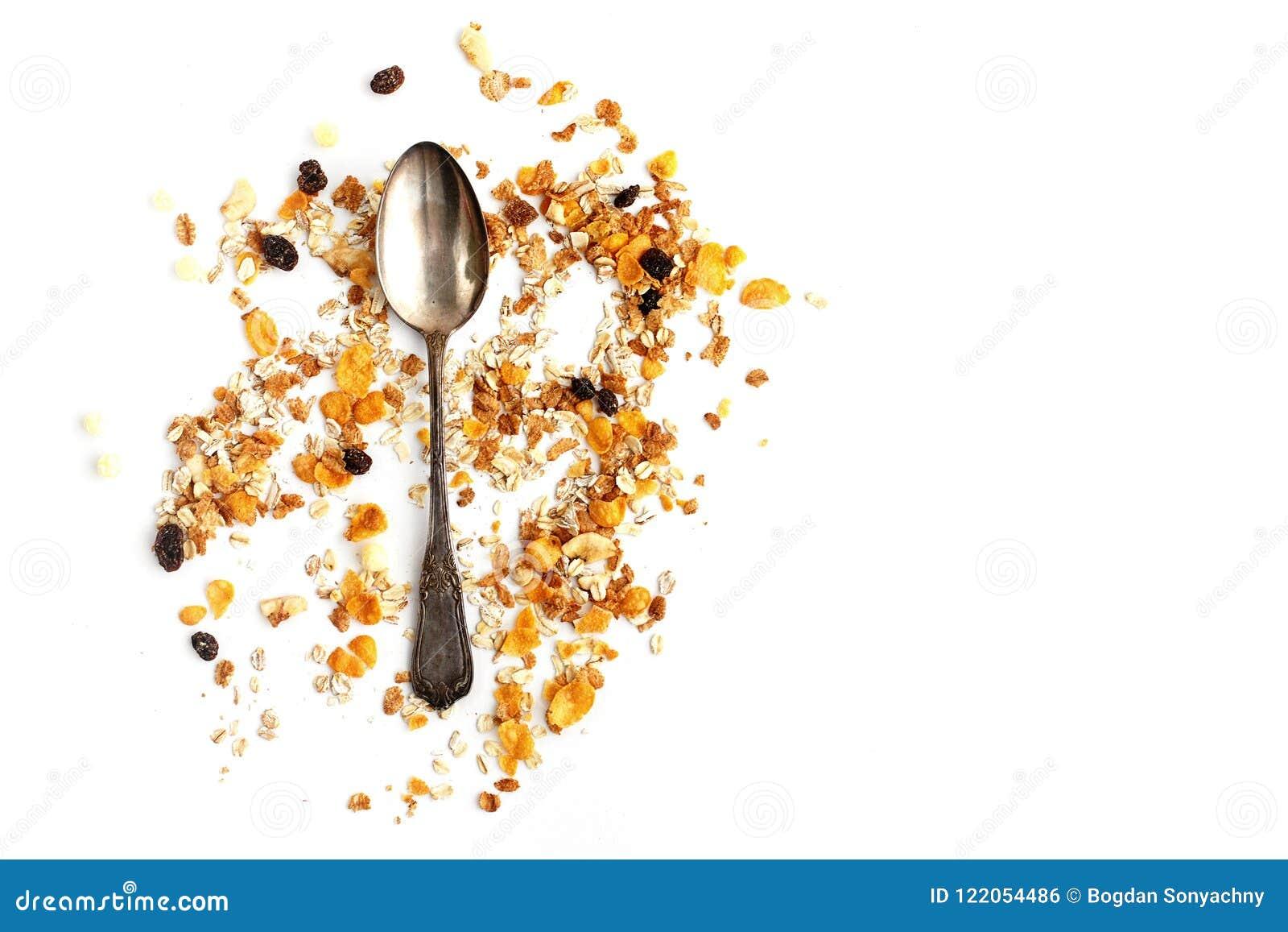 Cereal delicioso del muesli del granola con la cuchara del vintage en la parte posterior del blanco