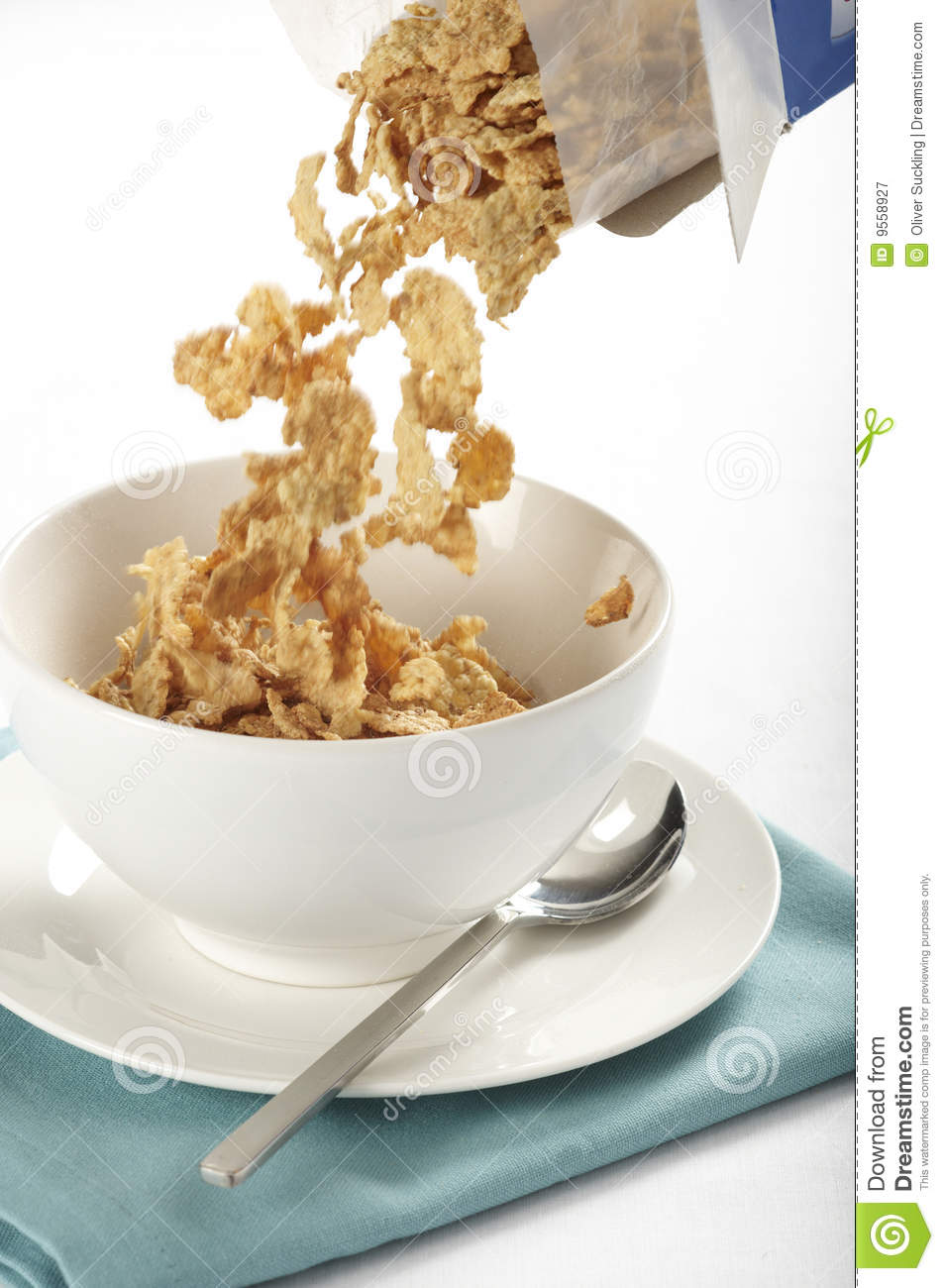 tabletop view of breakfast cereal flakes being poured from a box ...