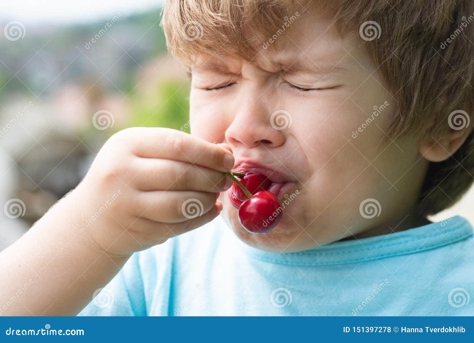 Cereja ácida, gosto ácido O bebê tenta primeiramente a cereja Crian?a emocional Alimento saud?vel Apetite Emoções do ácido sobre