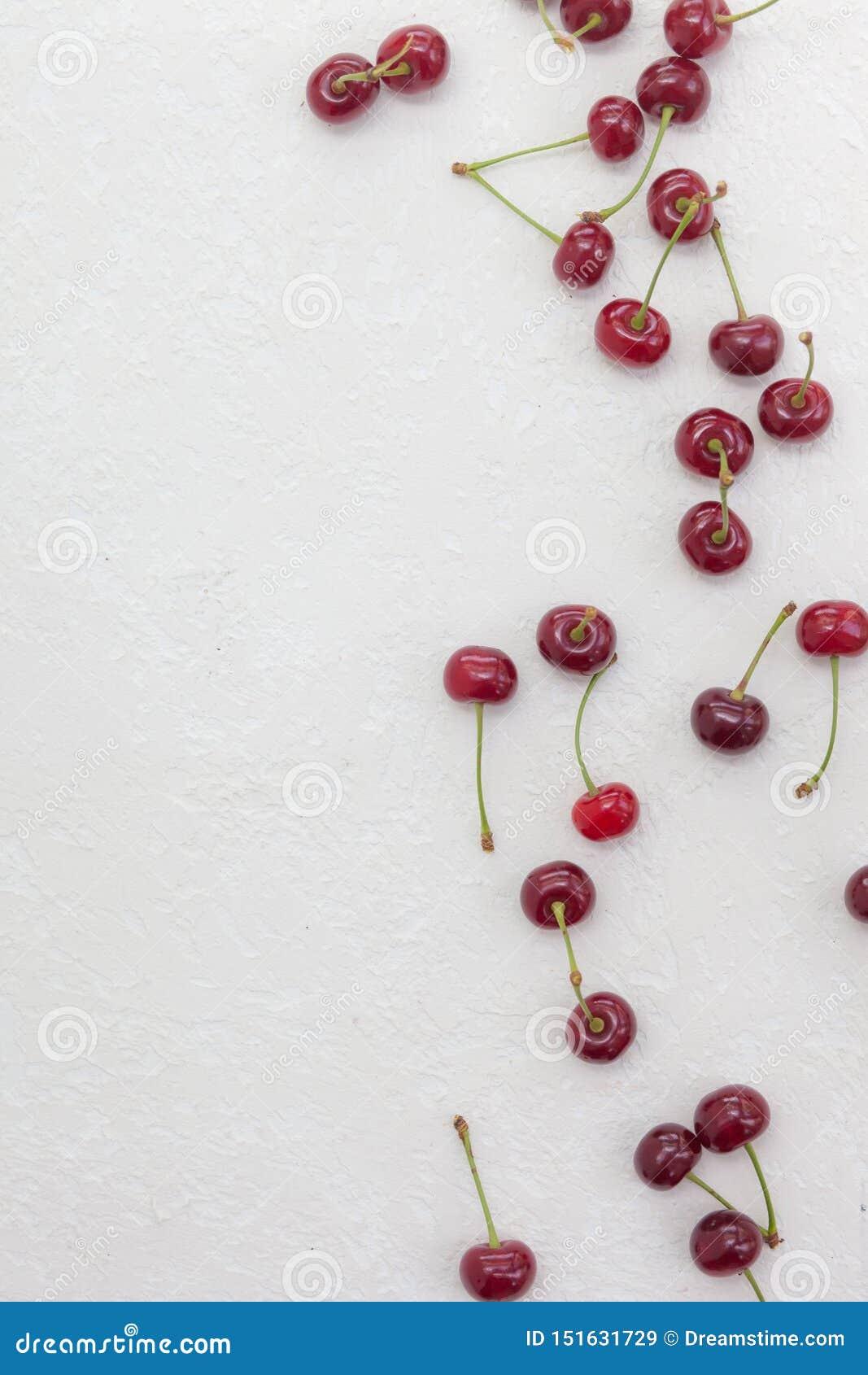 Cerejas grandes dispersadas em um fundo branco