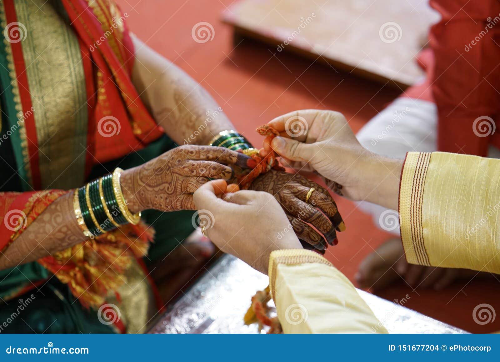 Ceremonia de matrimonio hindú tradicional donde hilo santo de las mareas del novio en la muñeca de la novia