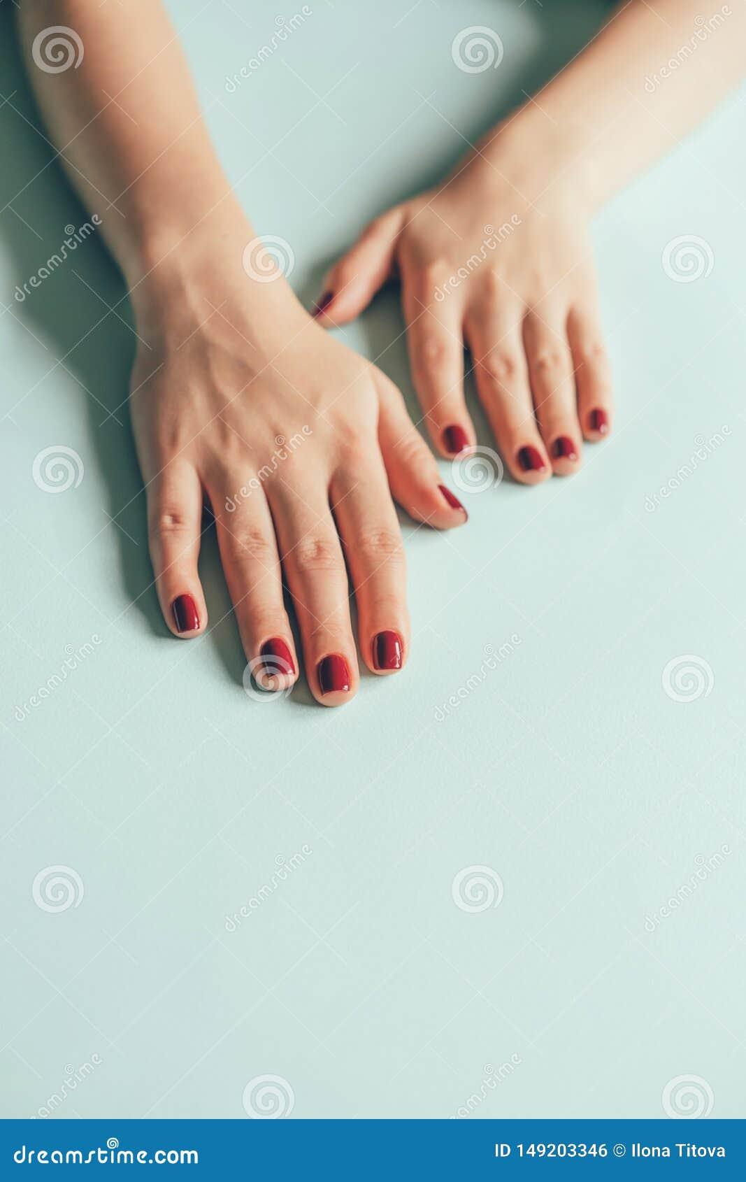 Cereza roja de la manicura de las manos