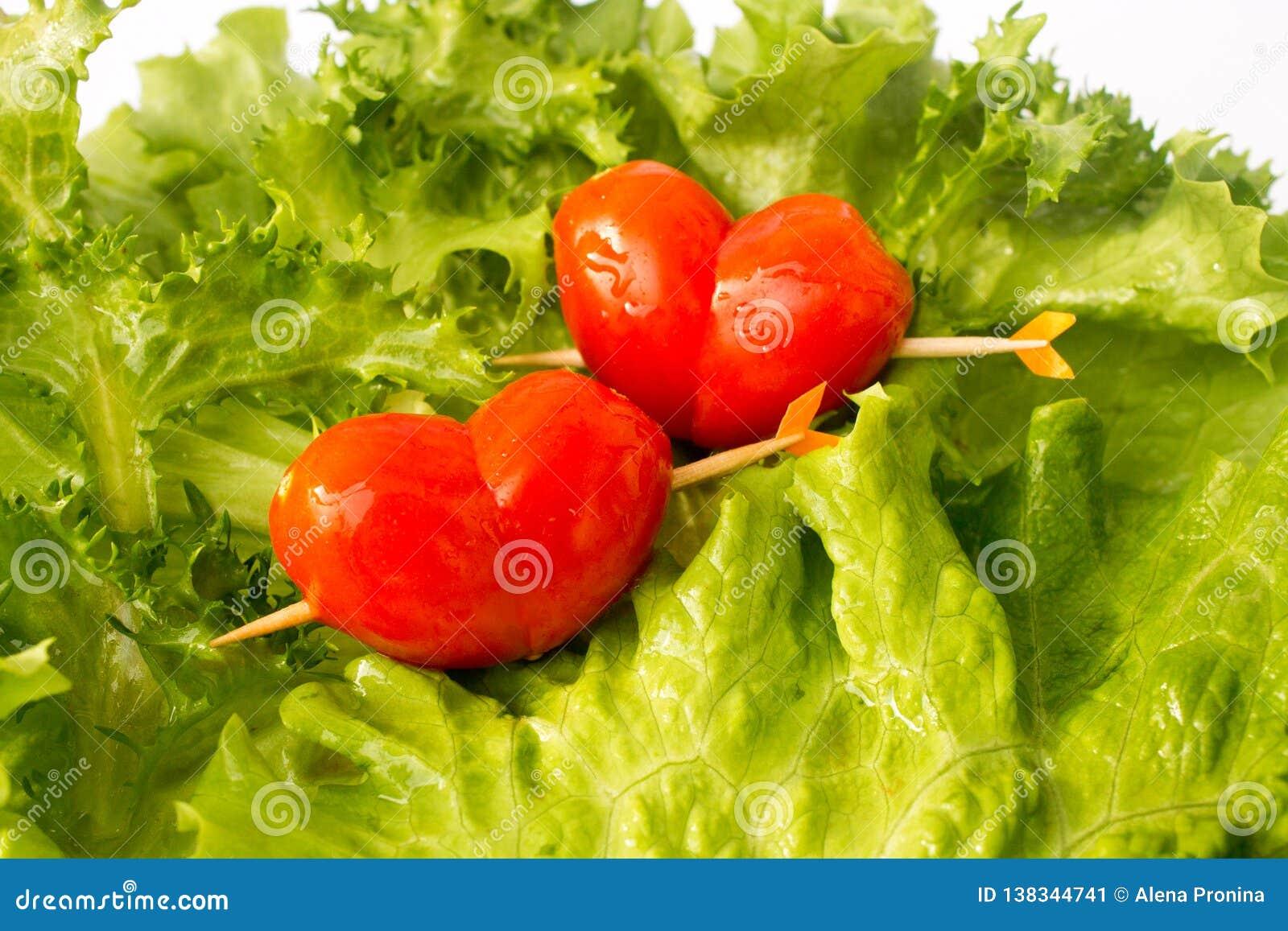Cereza roja del tomate dos en el slidce verde de la ensalada y del limón del iceberg