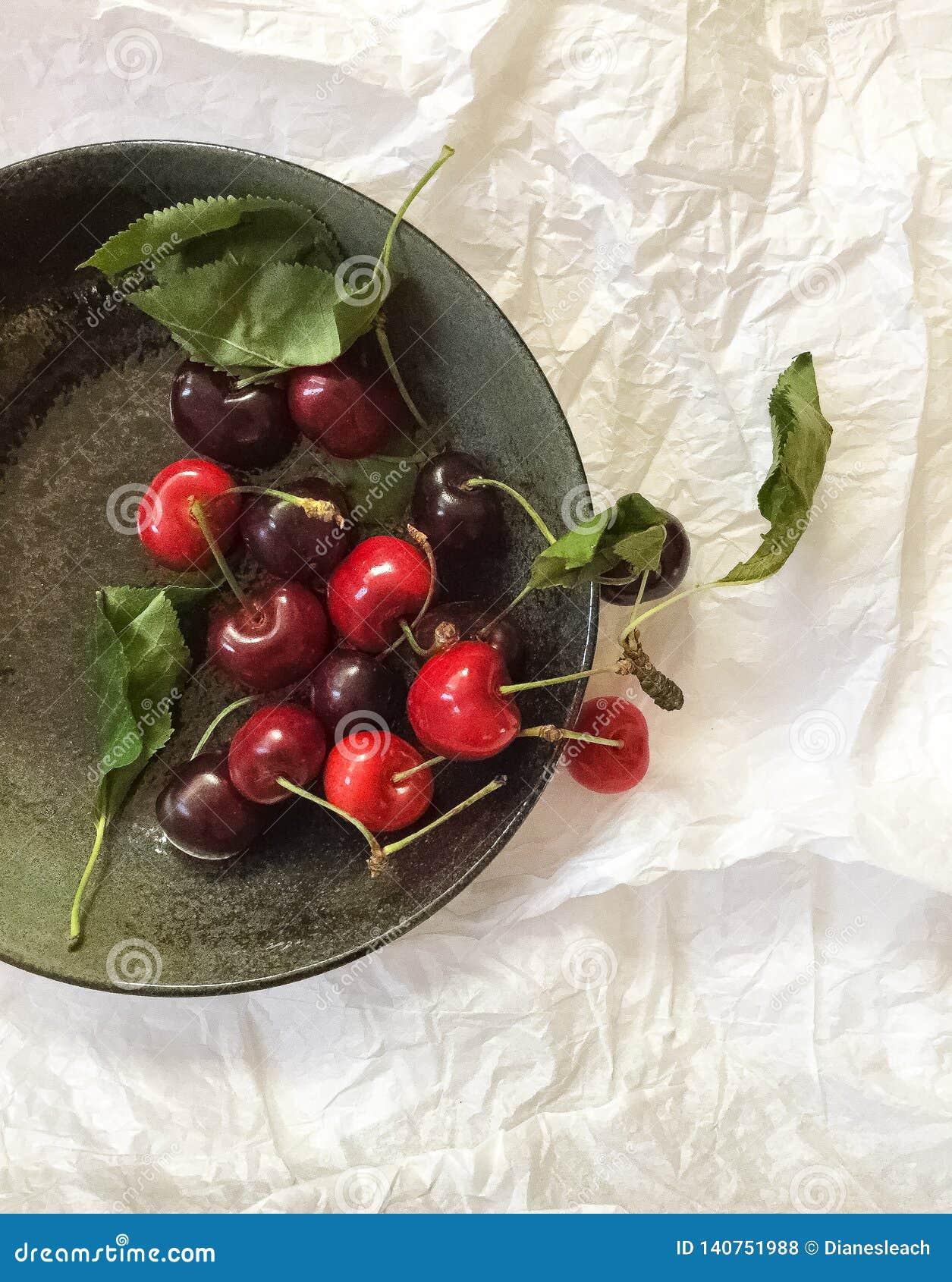 Cerezas rojas frescas en un cuenco gris, opinión superior, sobre un fondo blanco