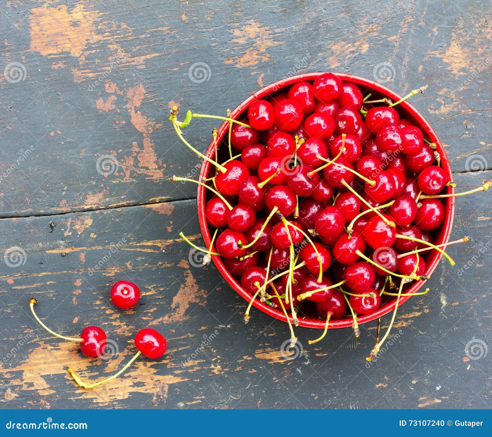 Cerises mûres rouges avec des queues dans un plat circulaire sur un vieux fond en bois noir avec une fente