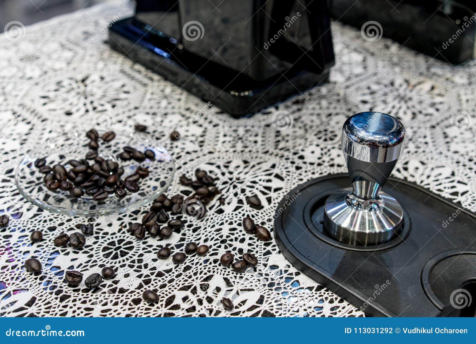 Cerrado encima de los granos de café del Arabica dispersó en el platillo de cristal en croc