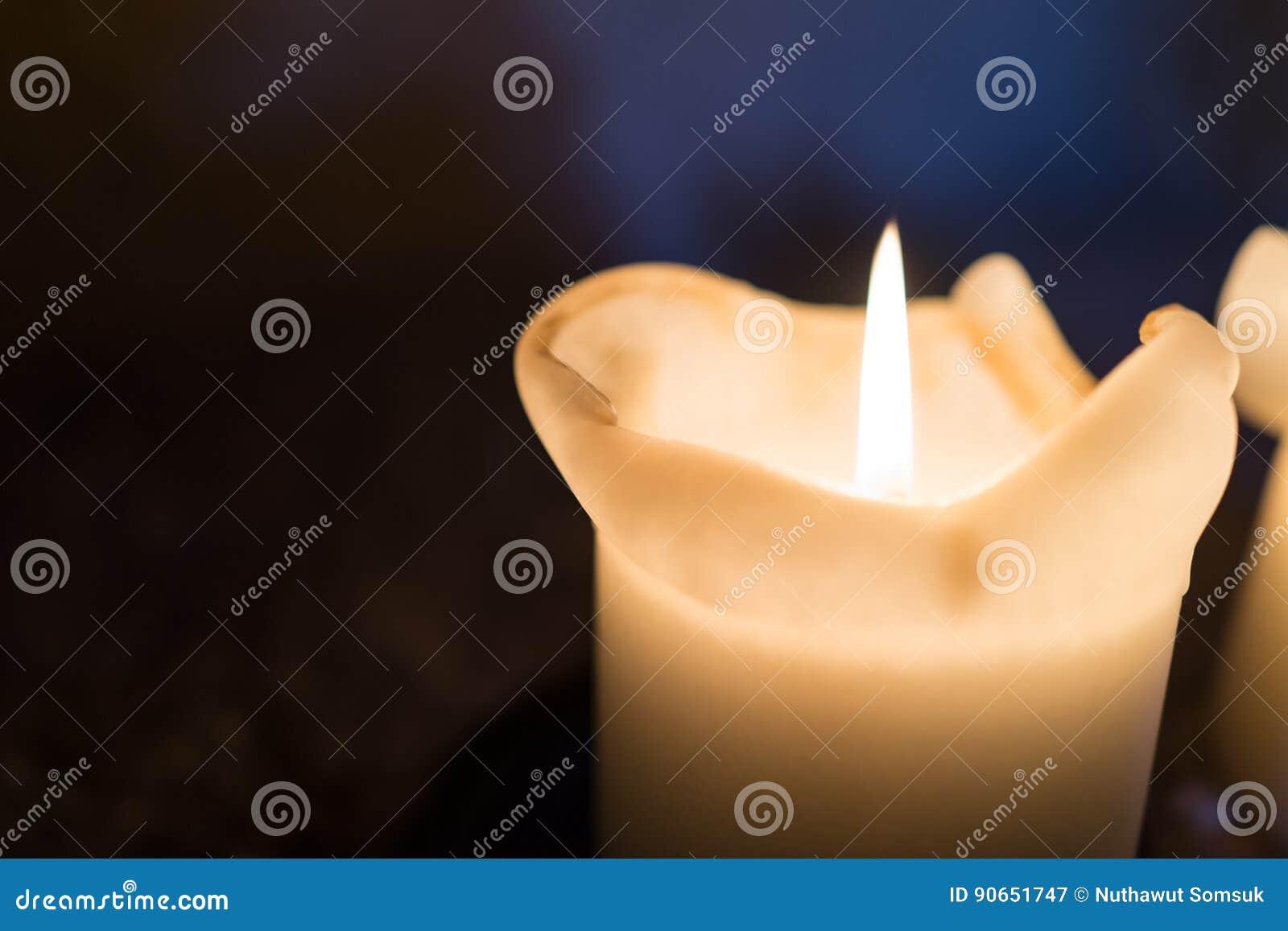 Cerrado para arriba de la luz de la vela de la iluminación borrosa en backgroun oscuro
