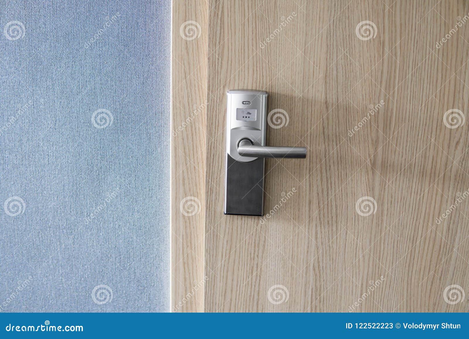 Cerradura electrónica del hotel en puerta de madera y con una pared azul