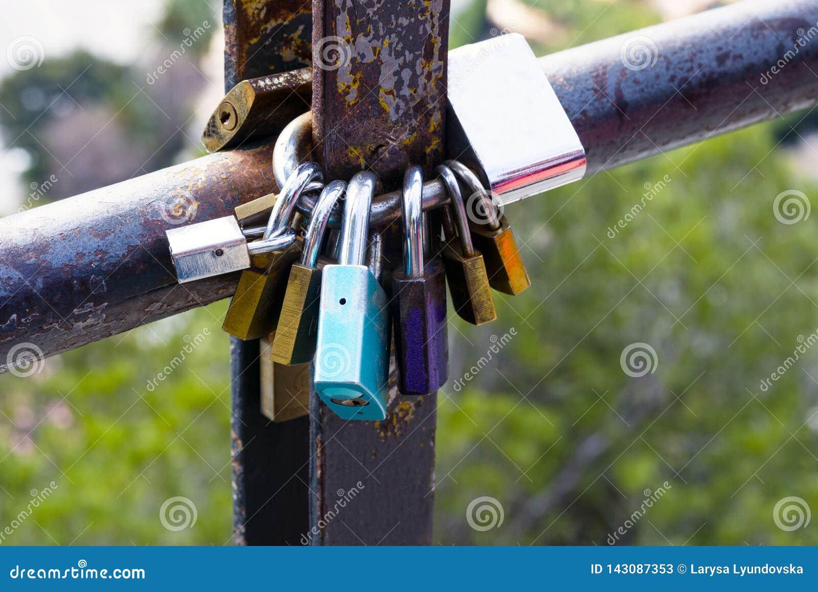 Cerraduras multicoloras del amor, cerradas en un tubo oxidado Símbolo del amor y de la lealtad