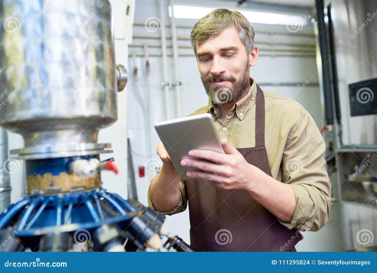 Cervecero hermoso con la tableta de Digitaces