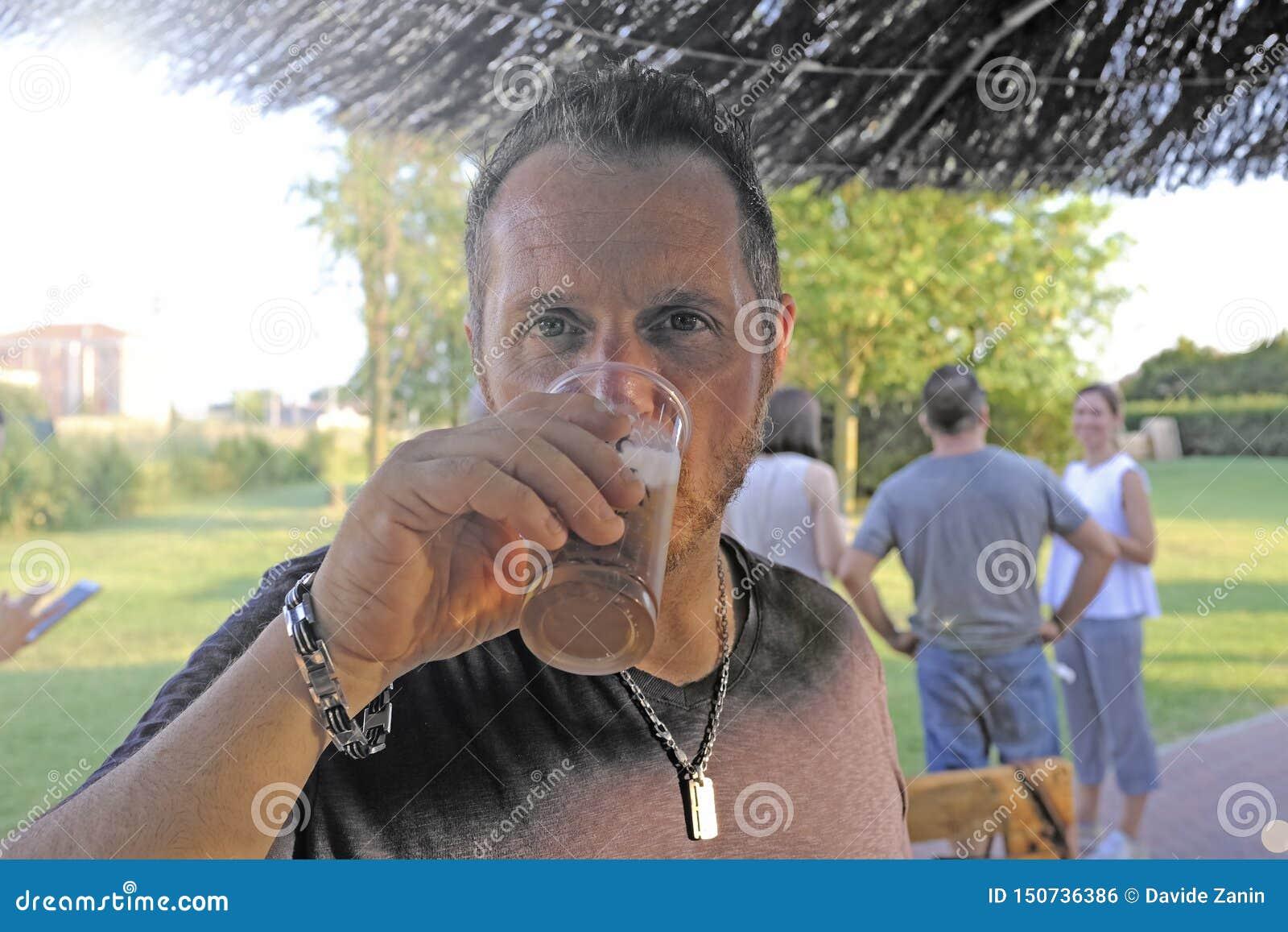 Cerveja bebendo do homem em uma barra exterior No fundo alguns amigos que apreciam Cerveja no vidro pl?stico