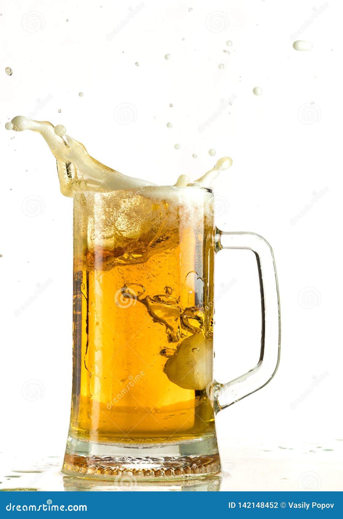 Cerveja clara de derramamento em uma caneca de cerveja, despeja a espuma e o pulverizador