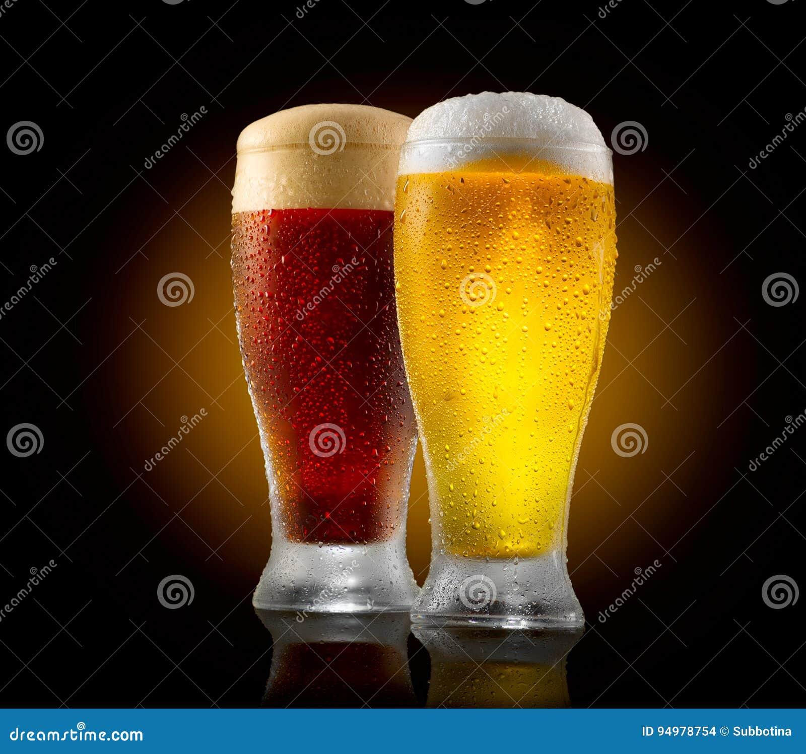 Cerveja do ofício Dois vidros da luz fria e da cerveja escura isoladas no preto