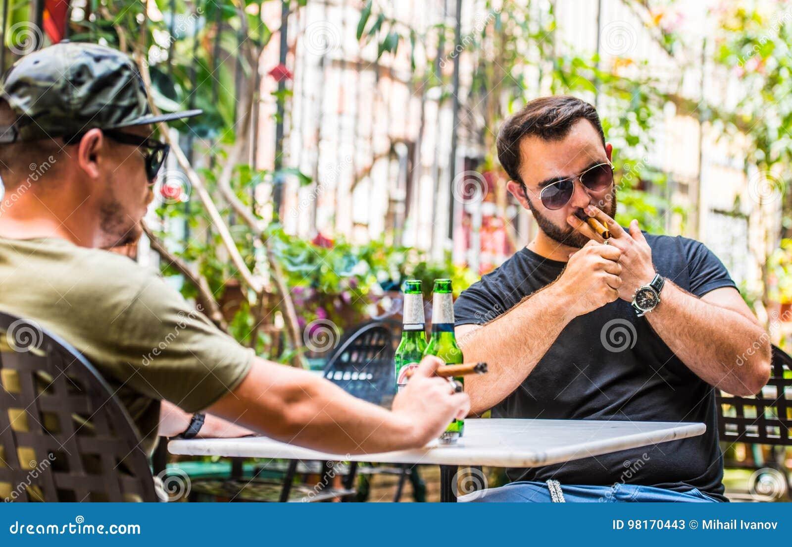 Cervejas bebendo e fumo de um charuto