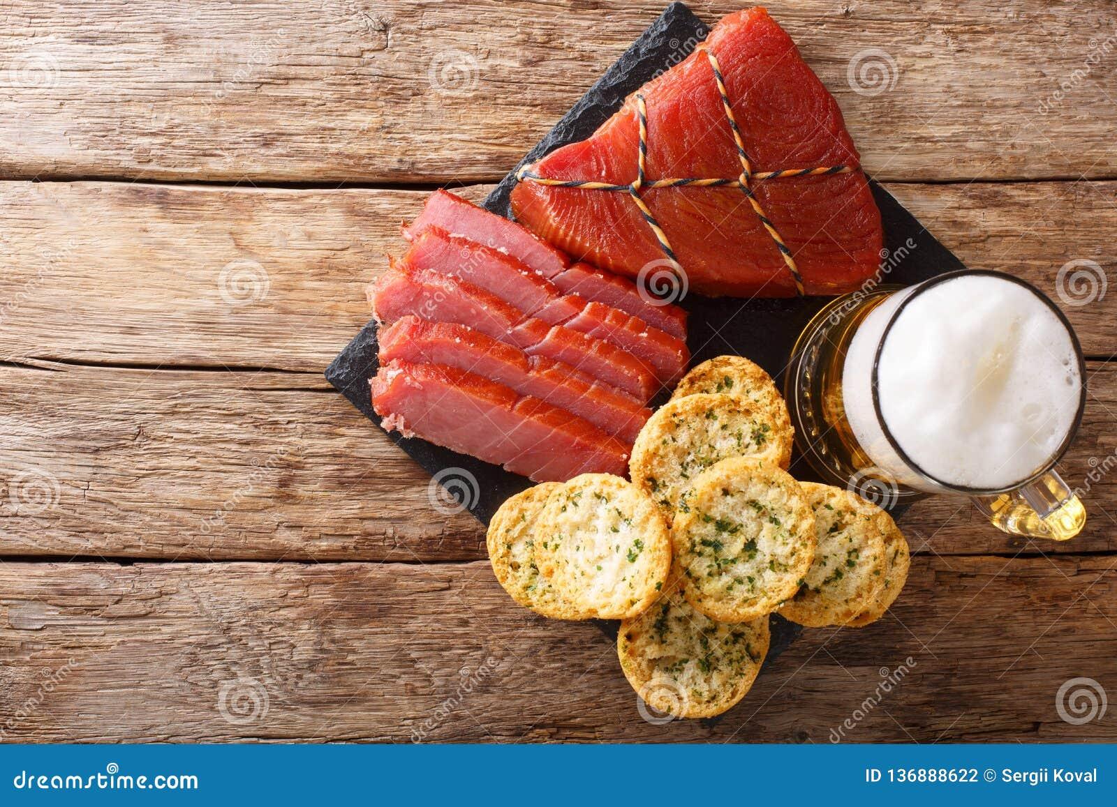 Cerveza ligera con espuma, el atún ahumado y la tostada con ajo y el primer de los verdes visión superior horizontal