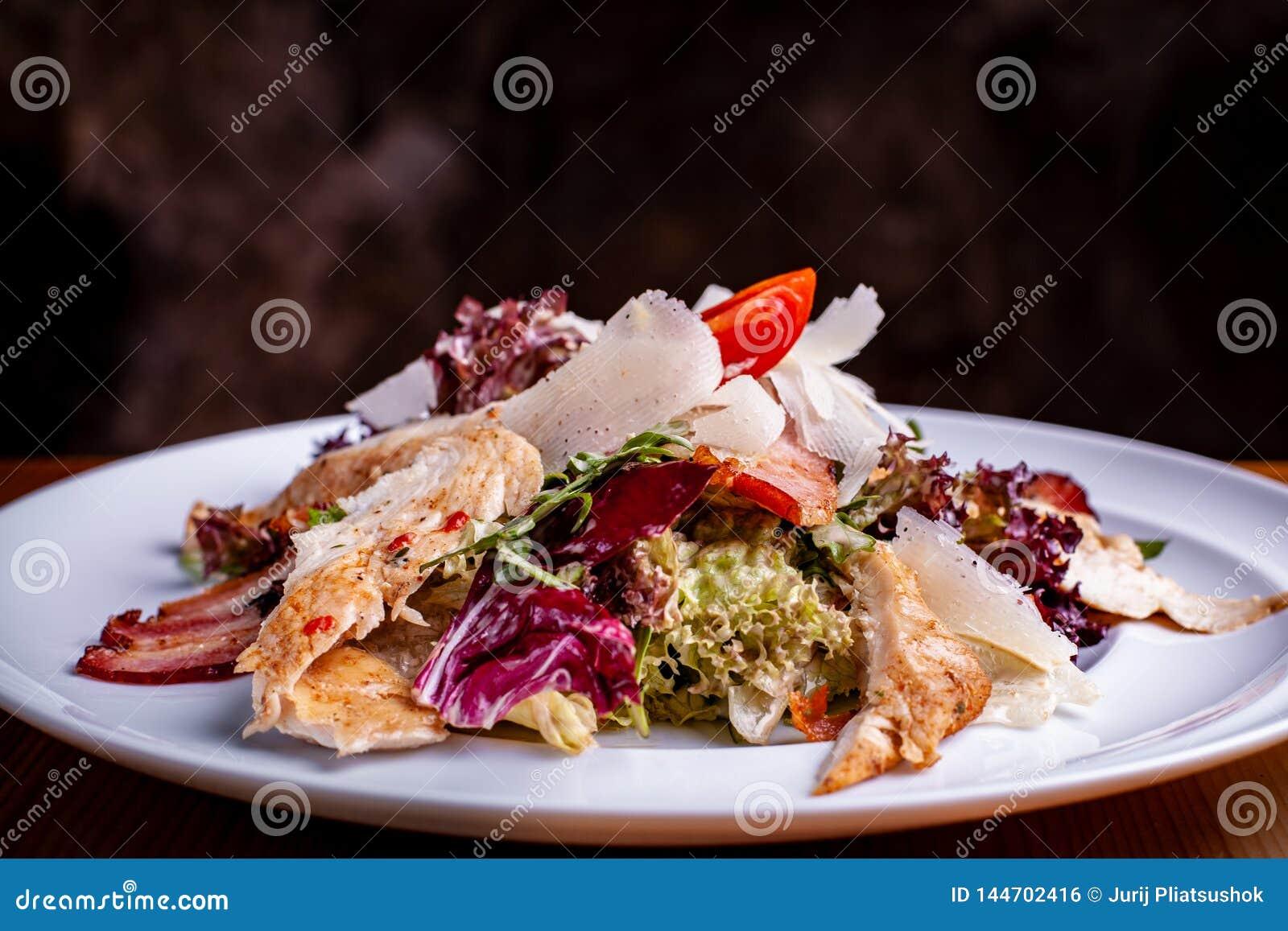 Cesar Salad en un cuenco de ensalada en un fondo del negro del restaurante