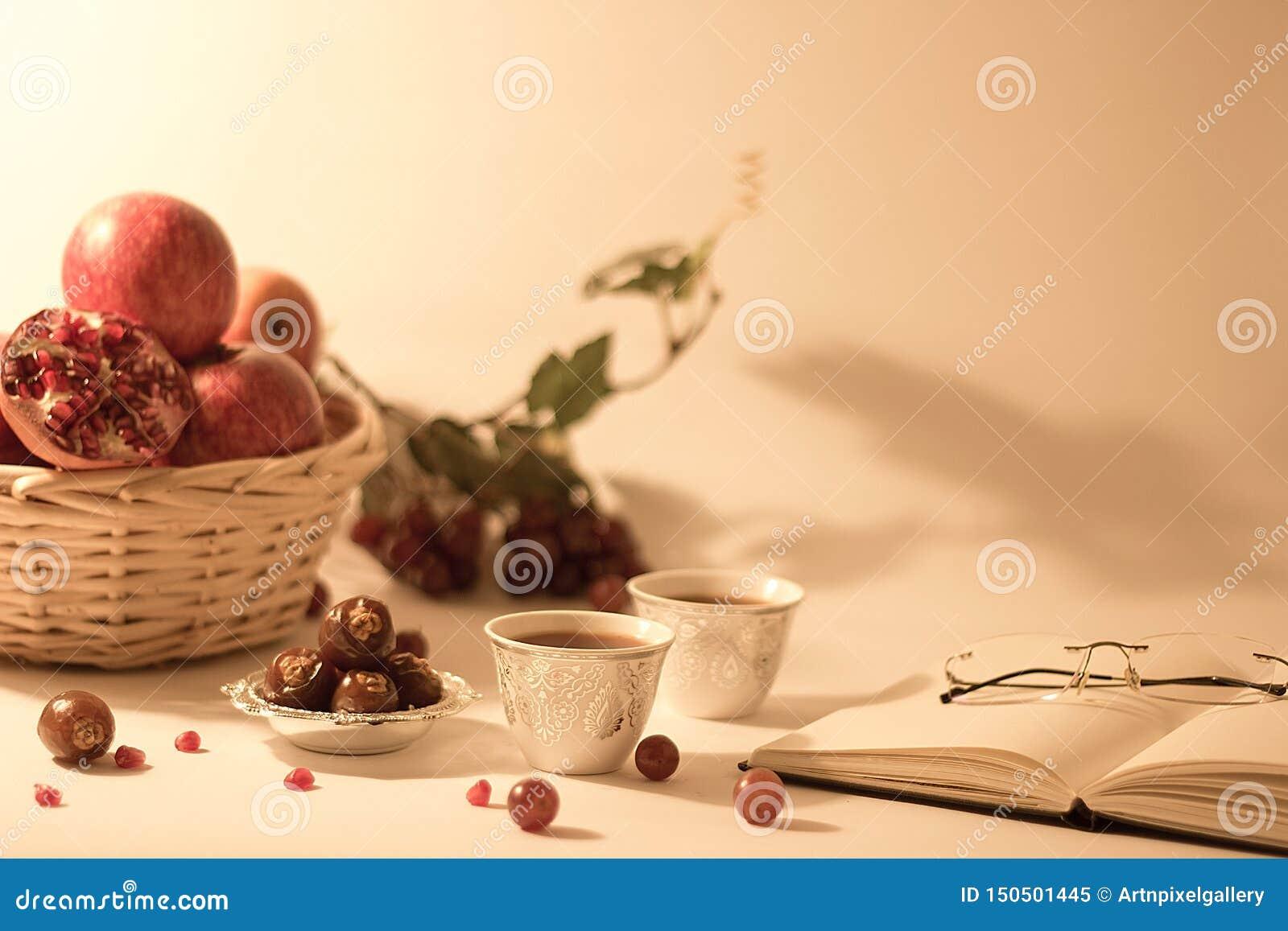 Cesta de fruto, datas em uma bacia de prata, copos de chá árabes com livro aberto e vidros de leitura