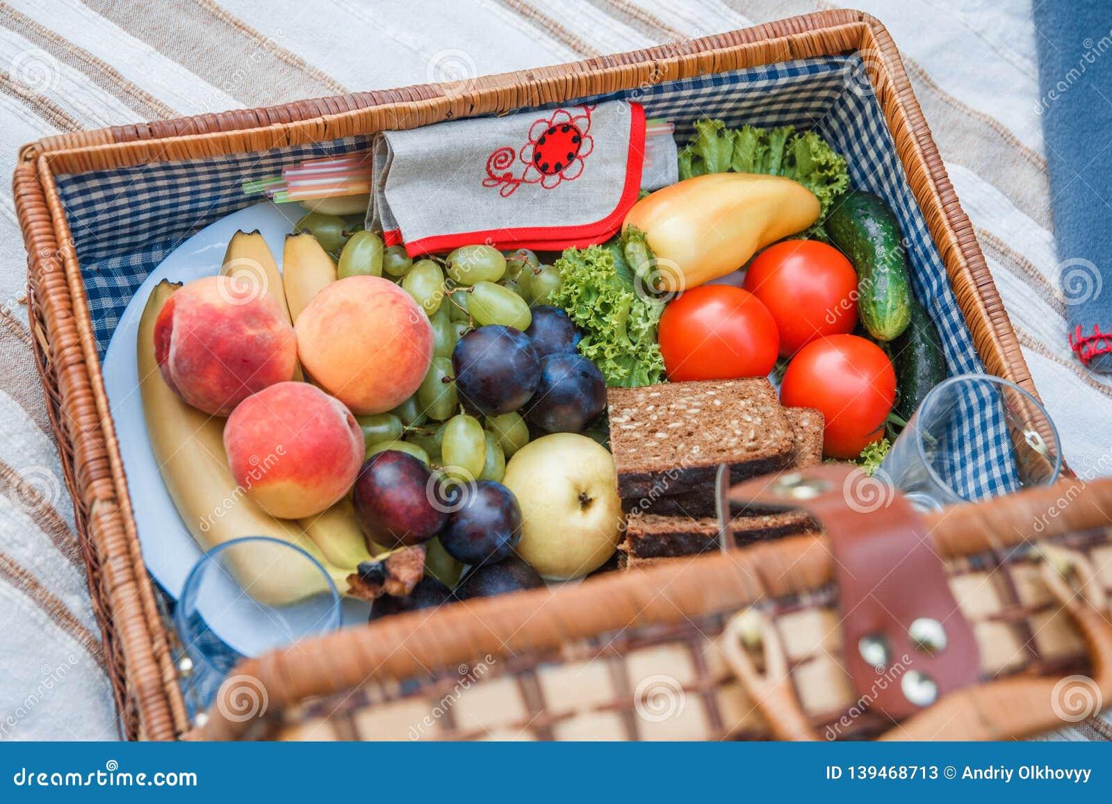 Cesta de la comida campestre con cierre de la fruta y del pan para arriba
