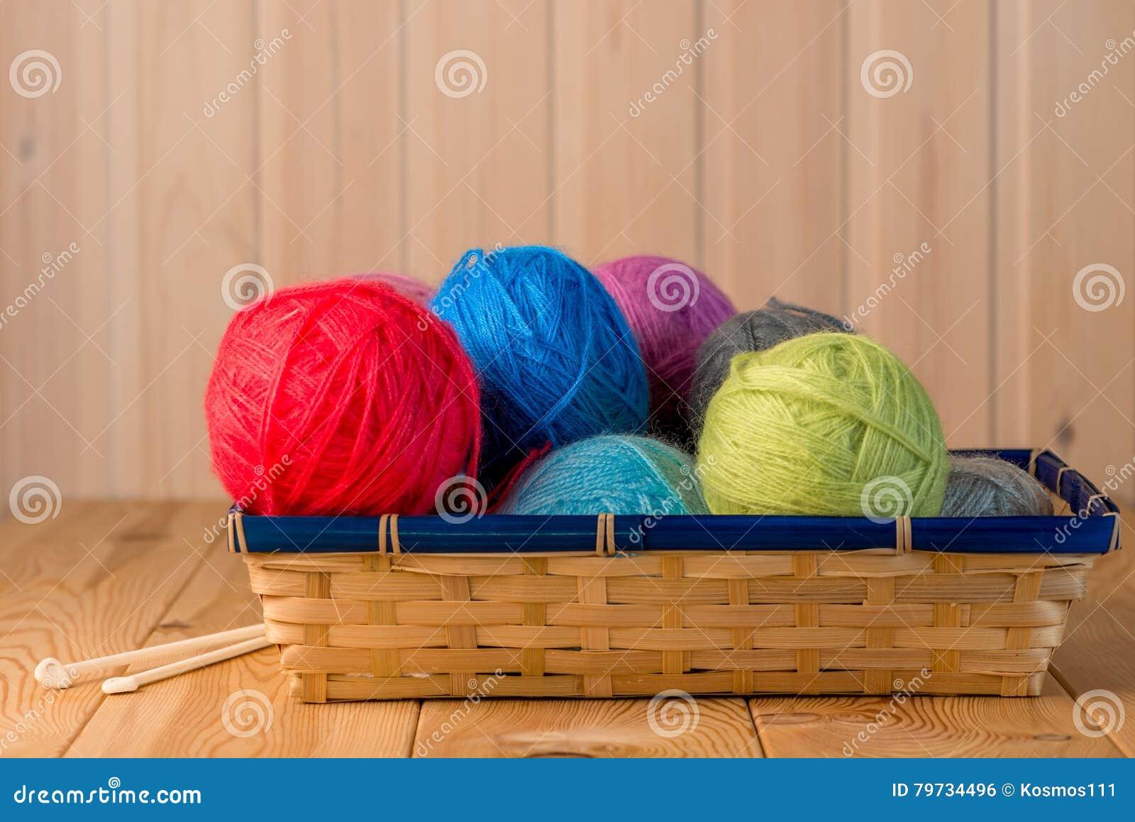 Cesta de la paja llena por completo de hilos de lana