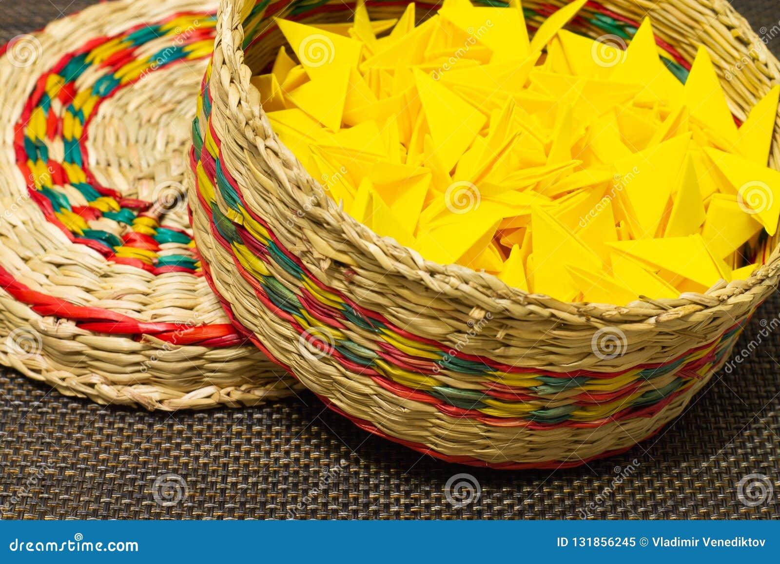 Cesta de paja tejida con el papel amarillo