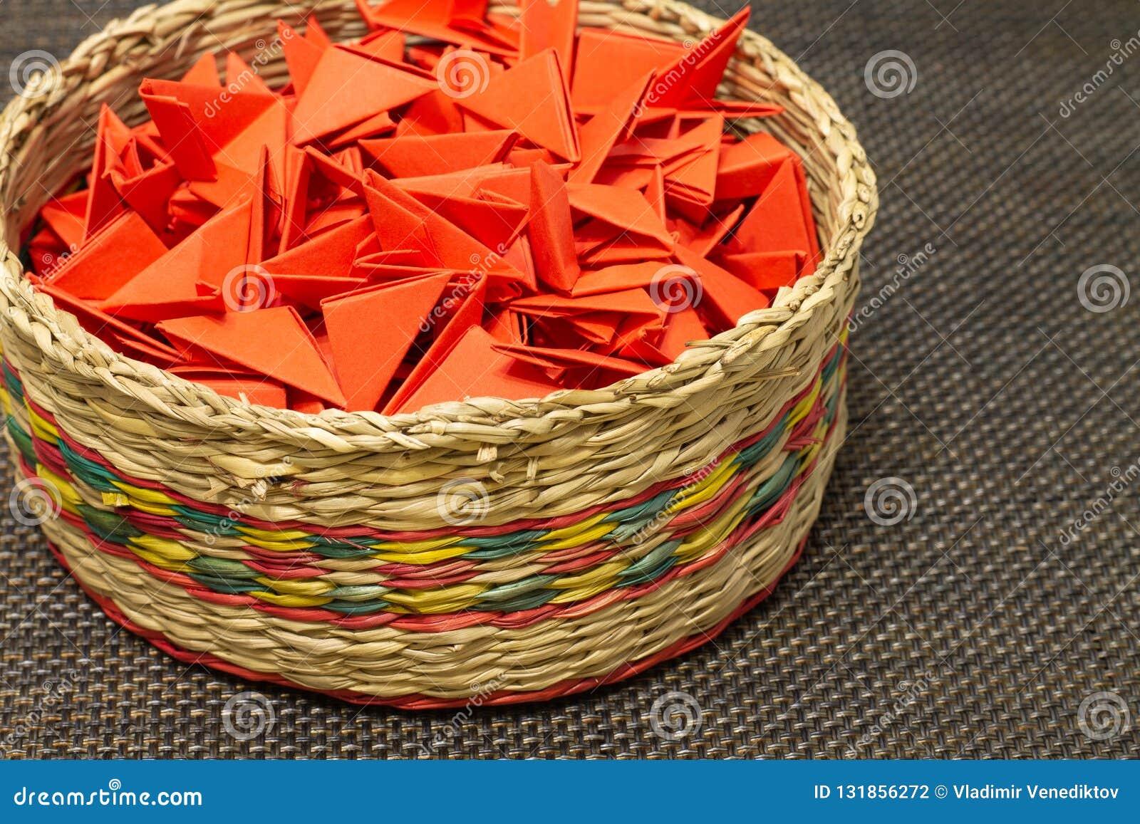 Cesta de paja tejida con el papel rojo