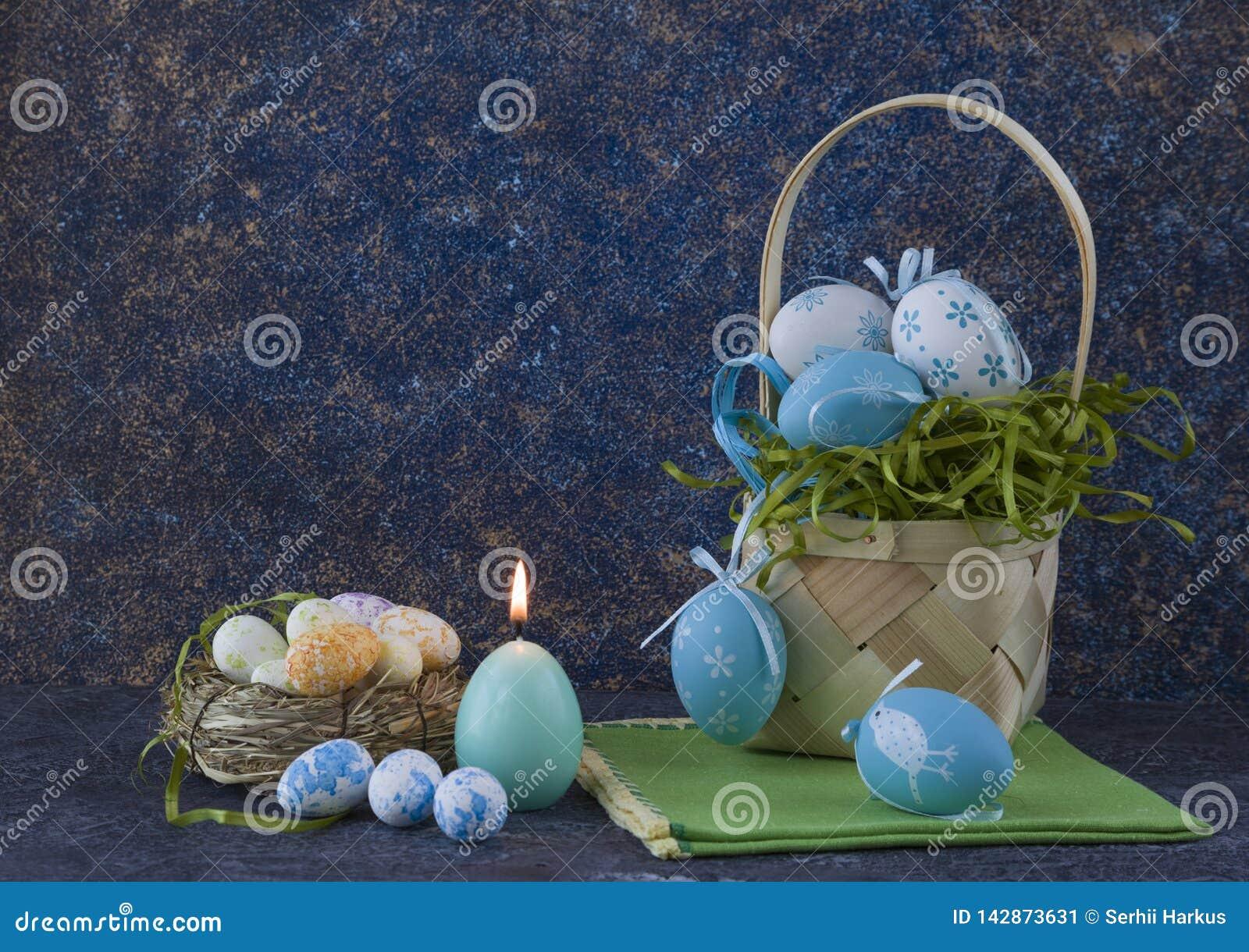 Cesta de Pascua con los huevos de Pascua coloreados en la tabla de piedra oscura