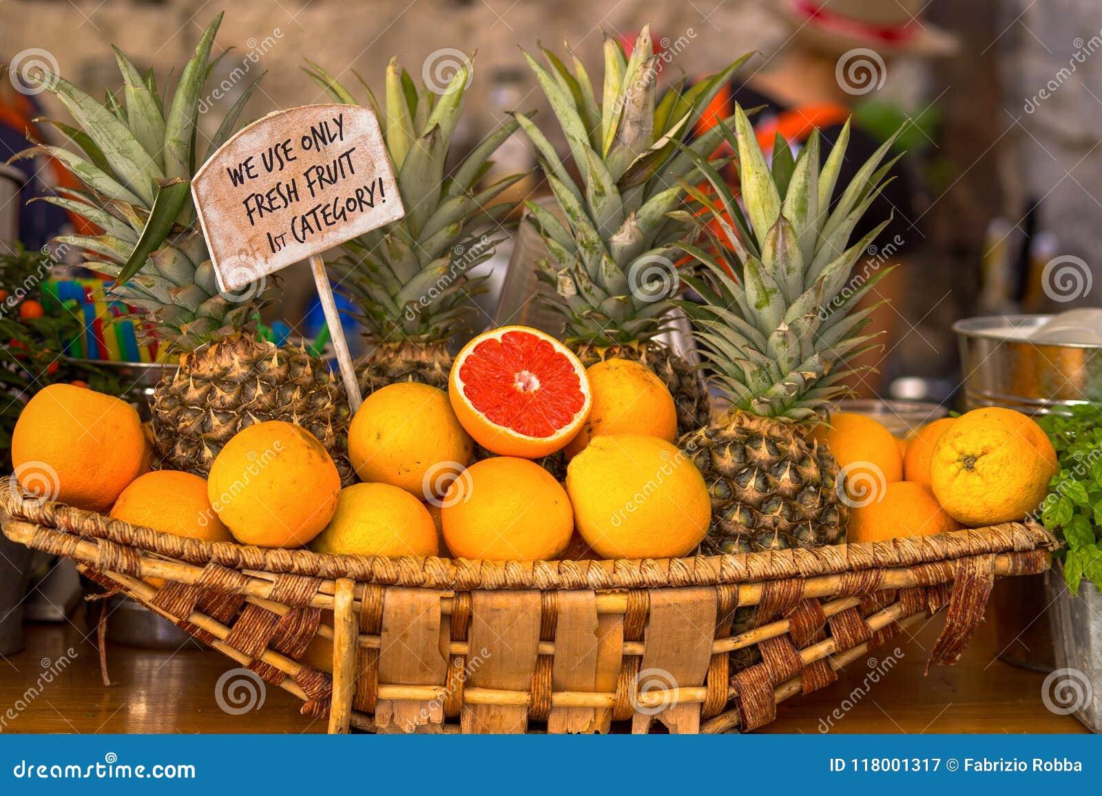 Cesta de vime com laranjas e abacaxis