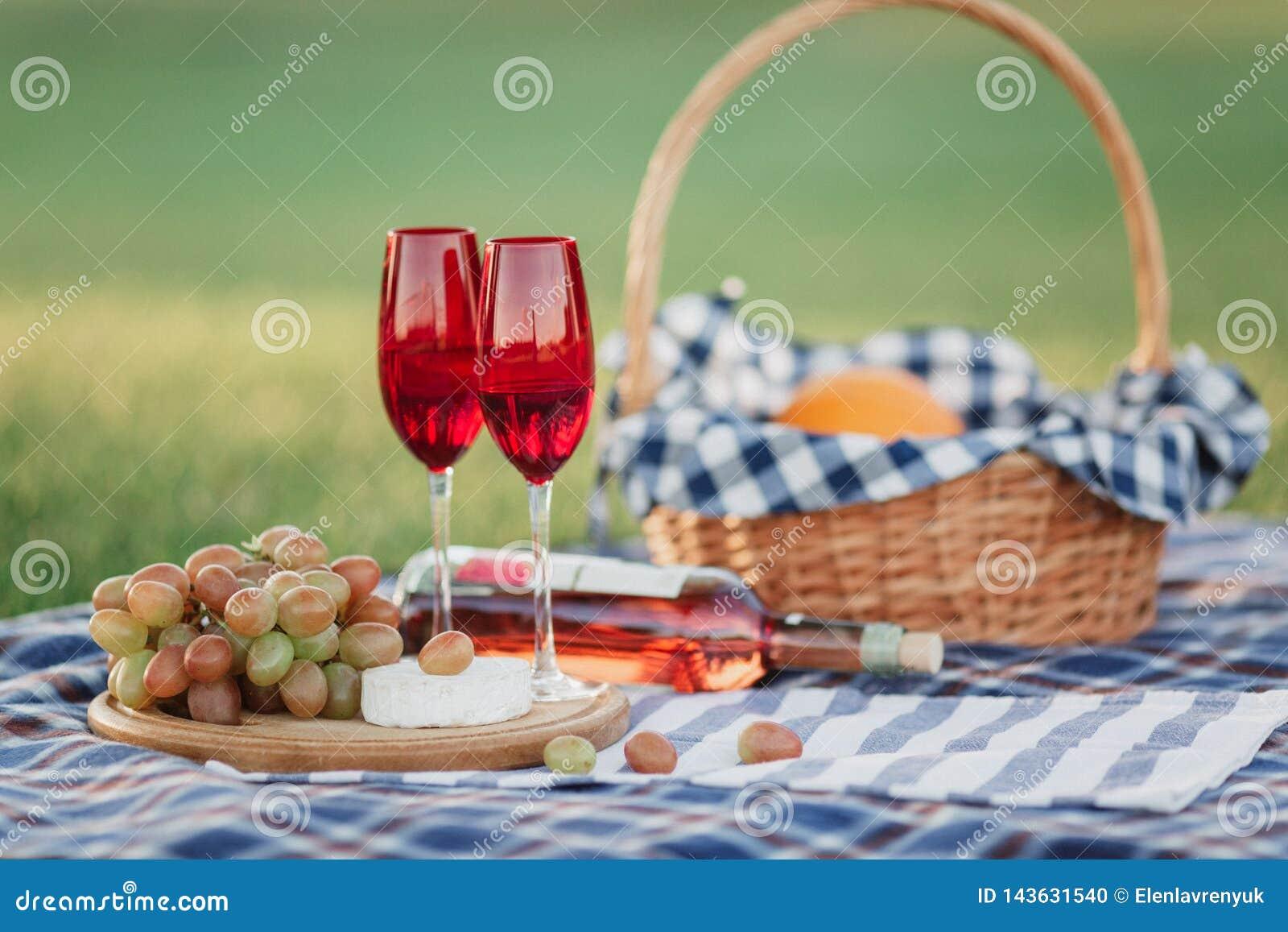 Cesta do piquenique com bebidas, alimento e fruto na parte externa da grama verde no parque do verão