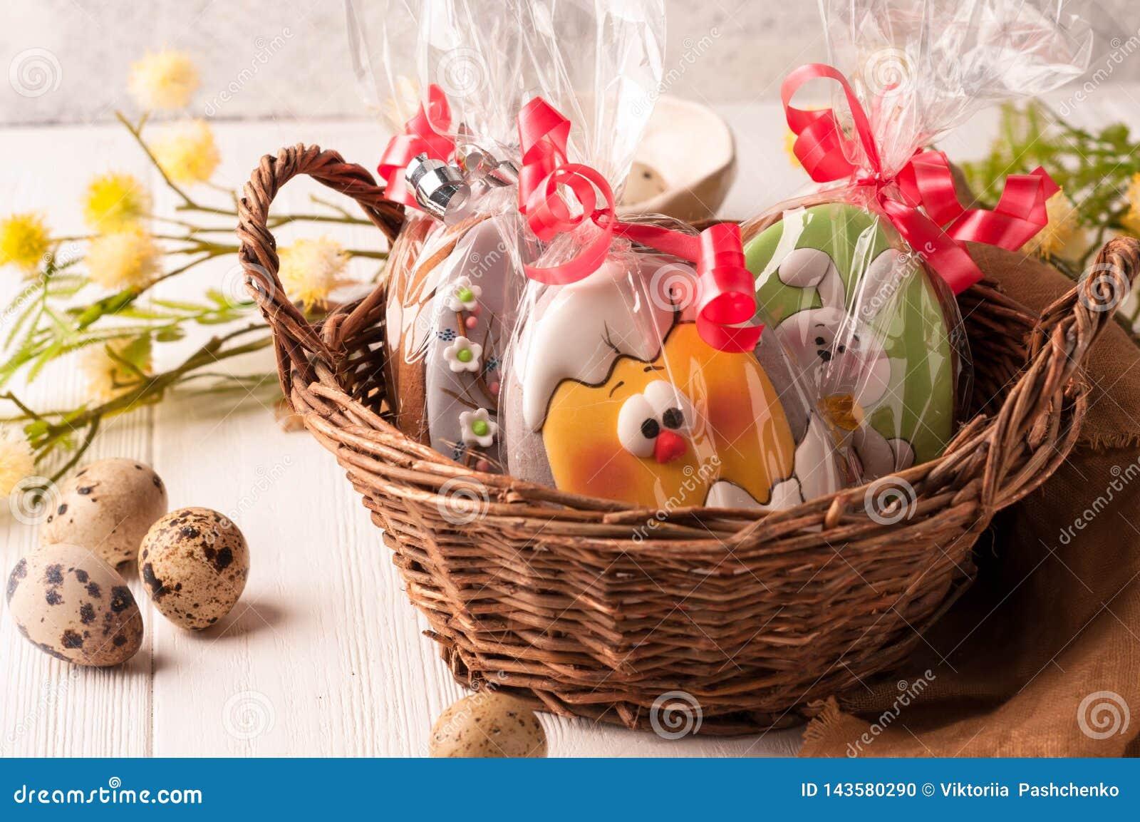 Cesta marrom de vime com as cookies envolvidas de easter perto dos ovos de codorniz e do ramo de florescência