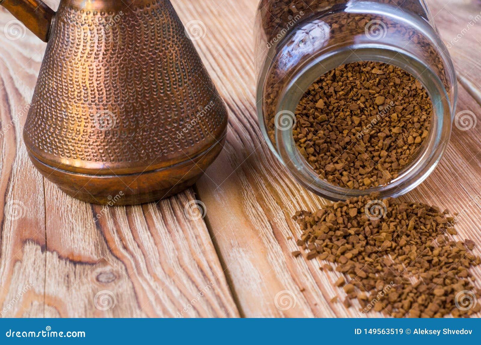 Cezve retourn? avec des grains de caf?, cuvette avec le caf? moulu sur la table en bois