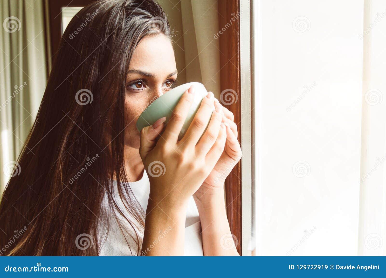 Chá bebendo de pensamento da mulher na janela