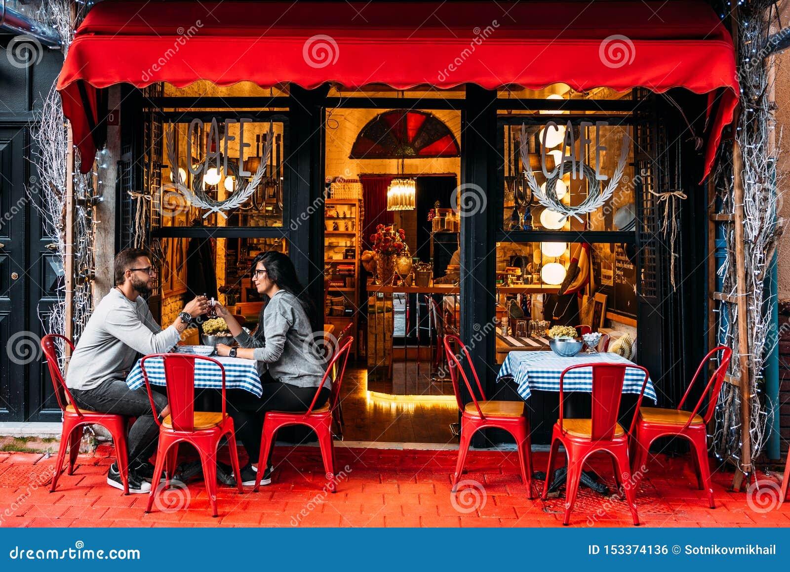 Chá bebendo dos pares felizes em um café da rua Pares no amor em um caf? Chá bebendo do homem e da mulher em um café Pares que se